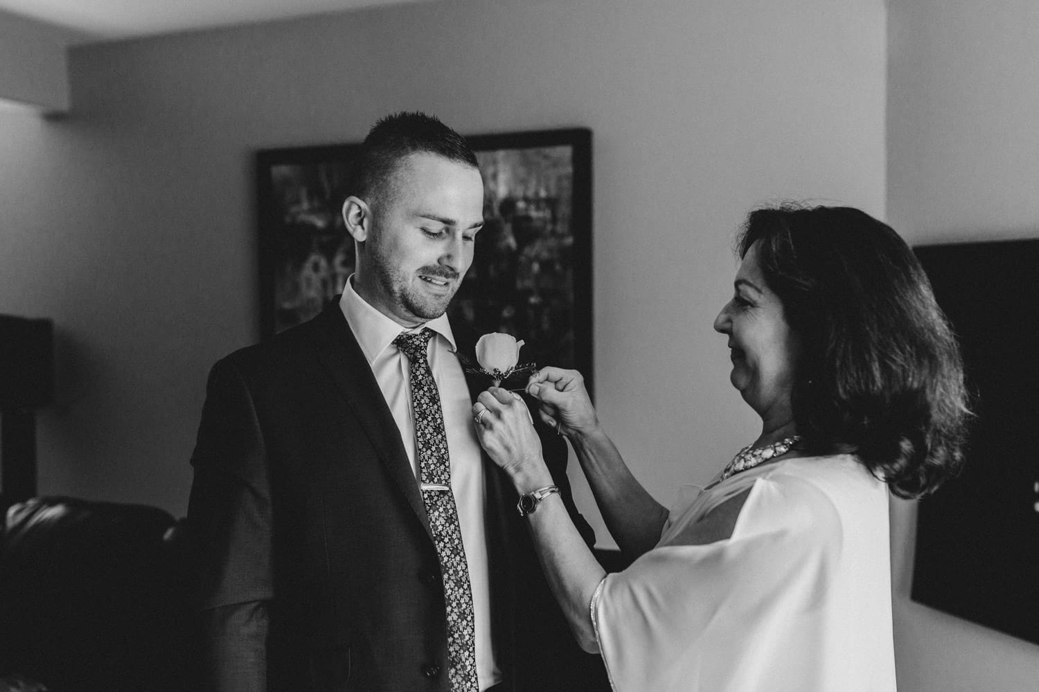 grooms mom helps pin boutonniere