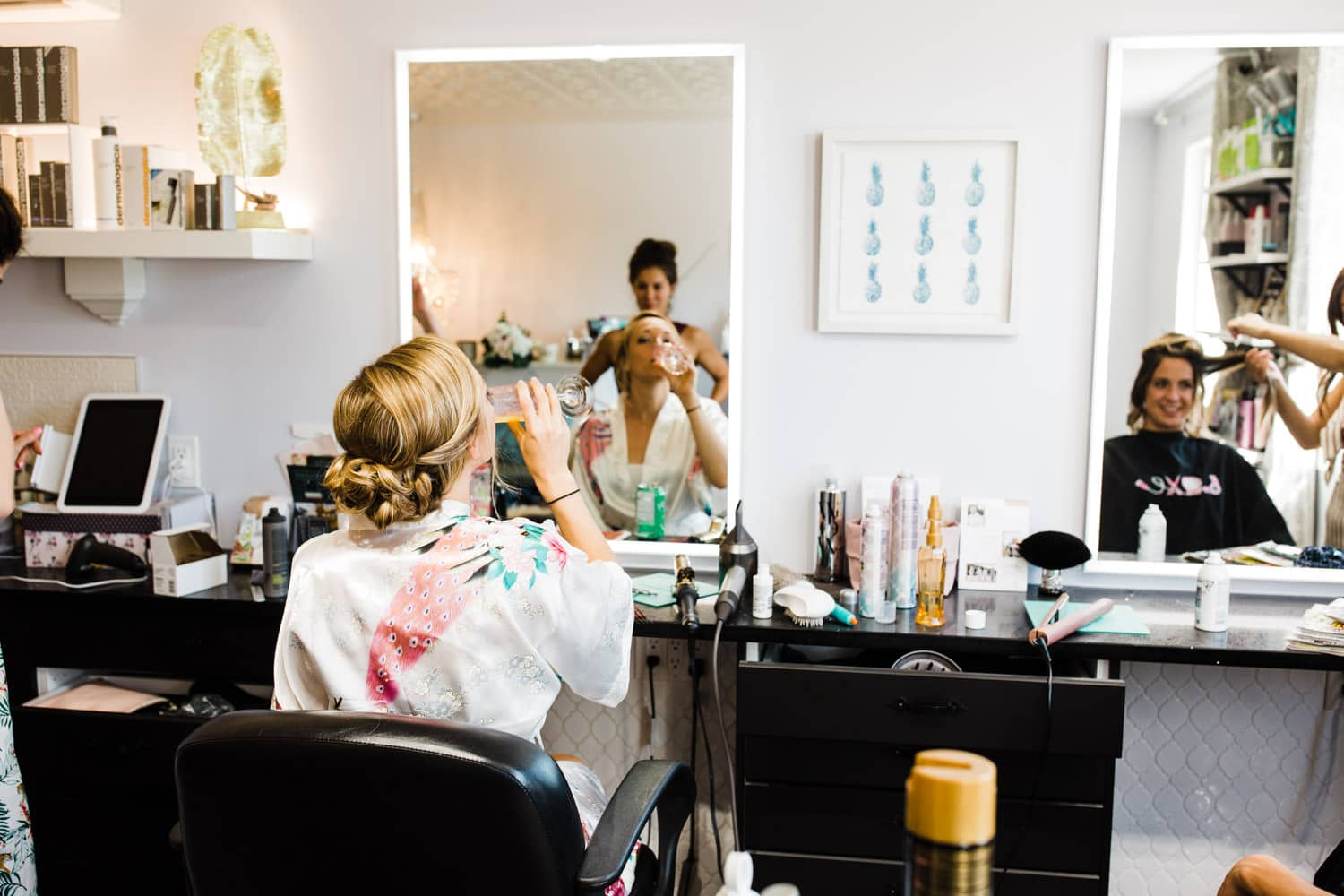 bride sips champagne during hair and makeup