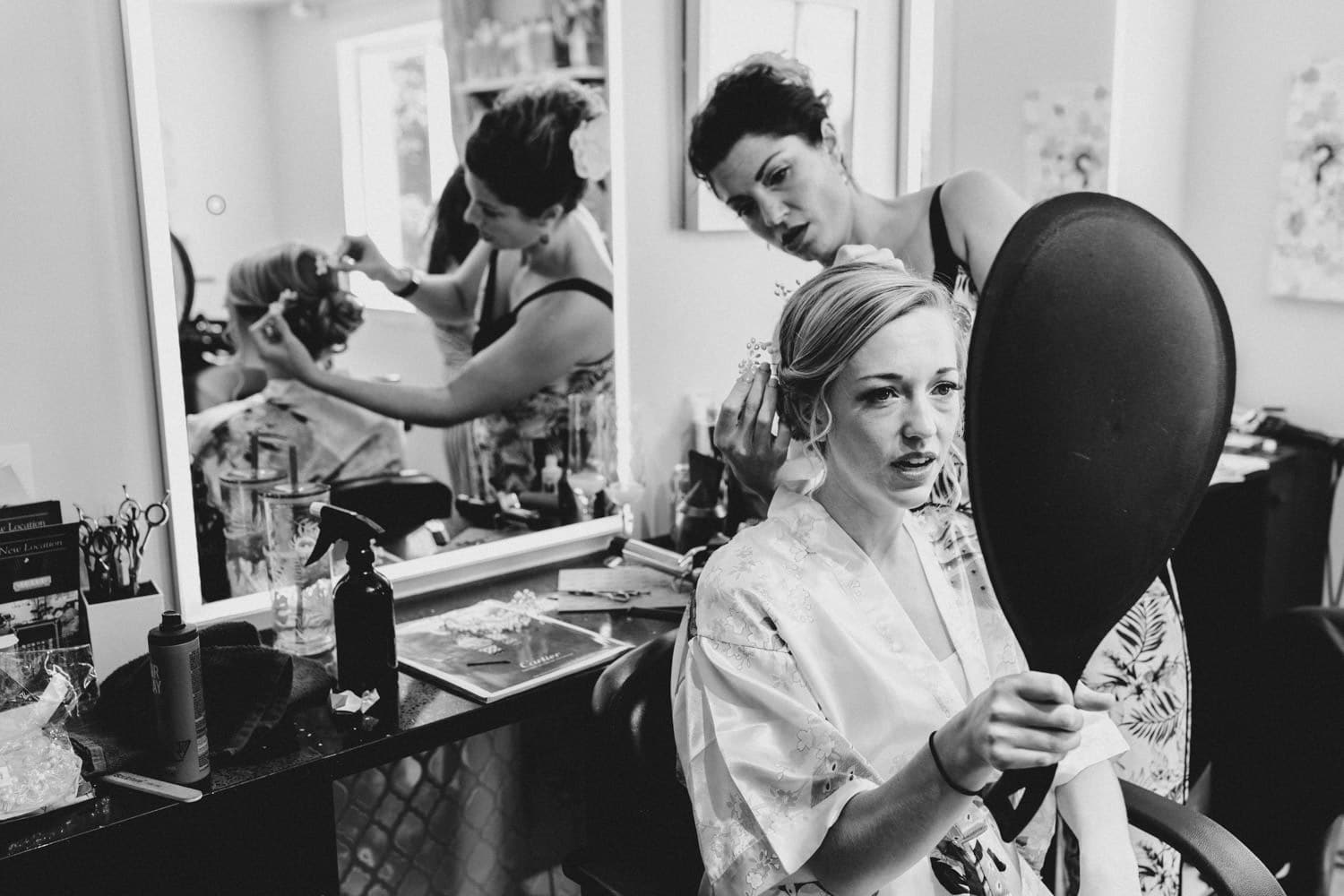 bride watches as hair dresses finishes her hair