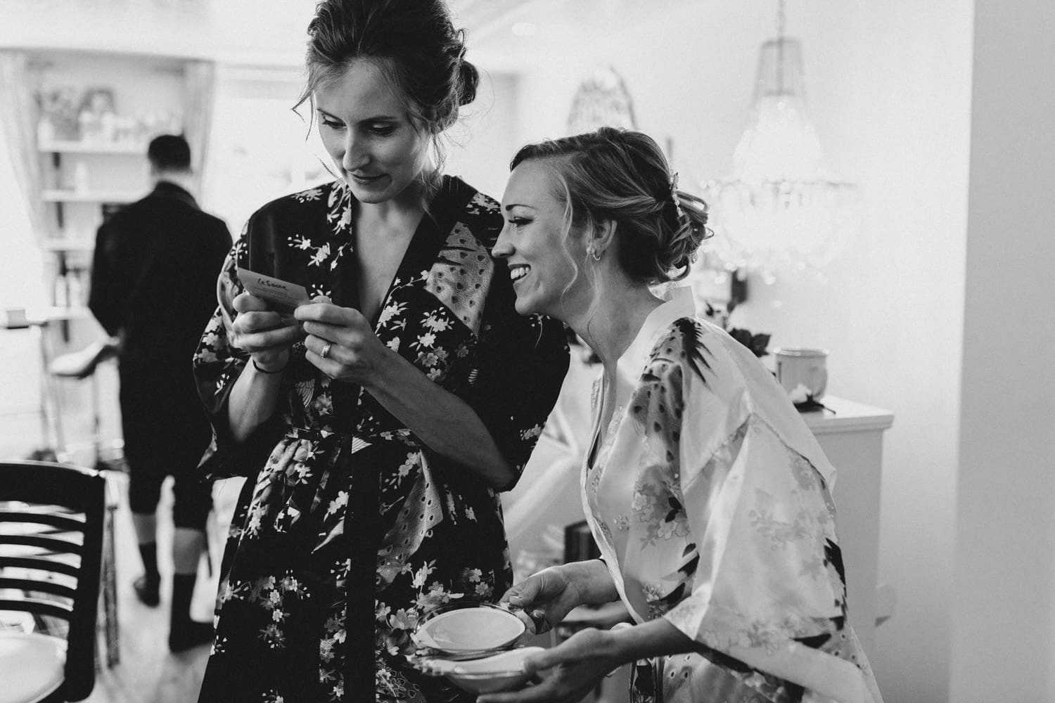 bride laughs with bridesmaid about stick-on bra