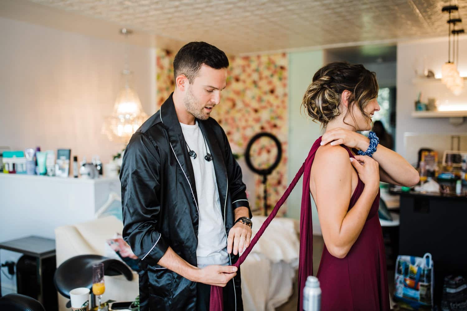 bridesman helps bridesmaid with her dress