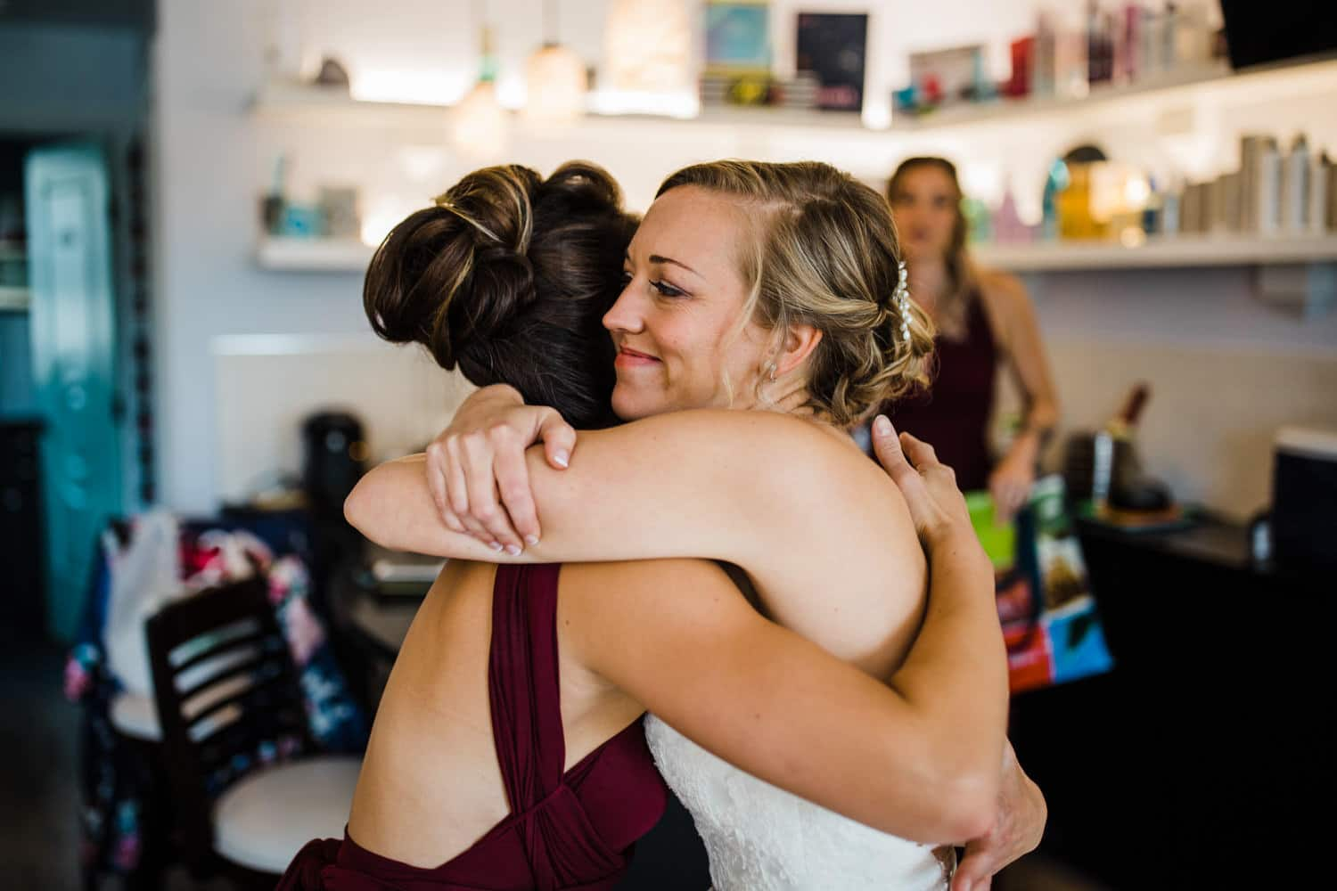 bride hugs bridesmaids morning of her wedding