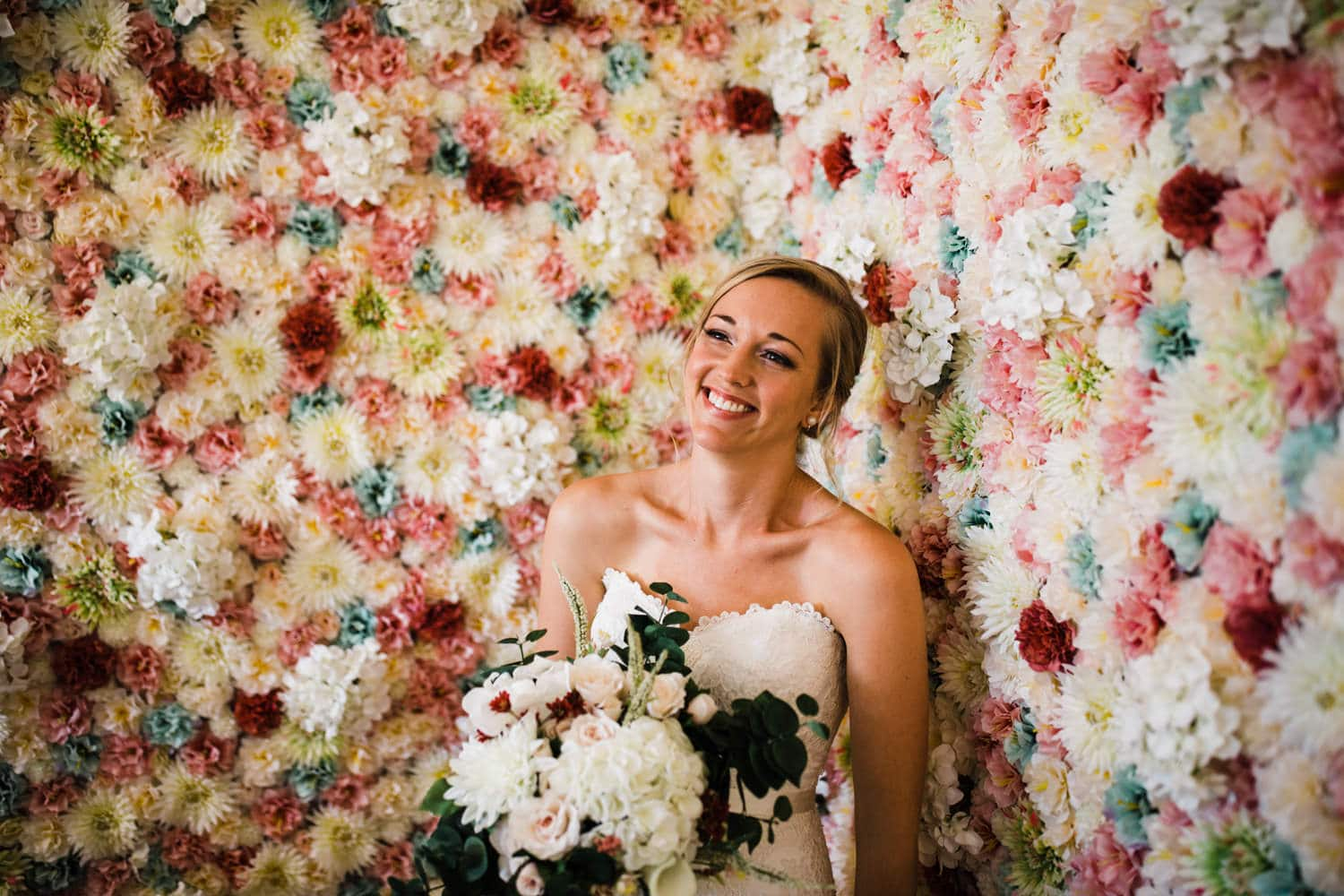 bride laugh in front of floral wall - ottawa wedding photographer