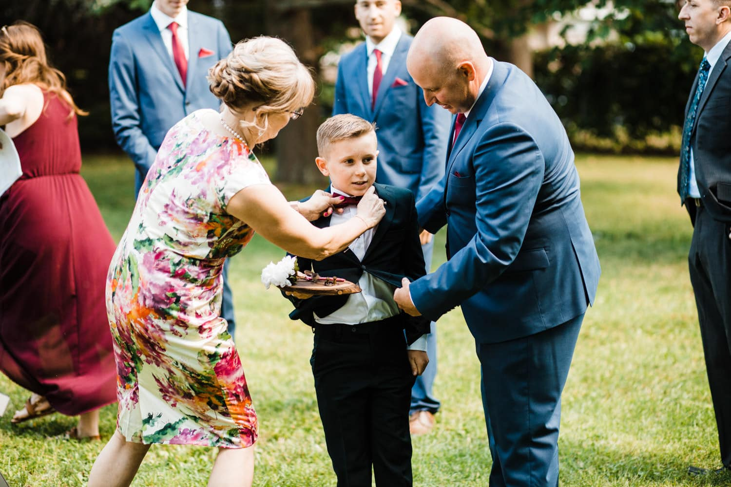 man and woman help adjust ring bearer's suit before wedding ceremony - glebe community centre wedding