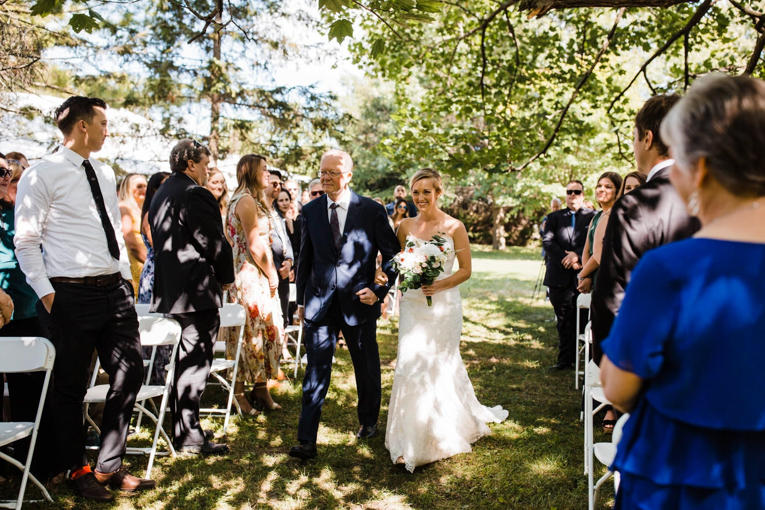 bride walks down aisle under trees - fairfield heritage house wedding