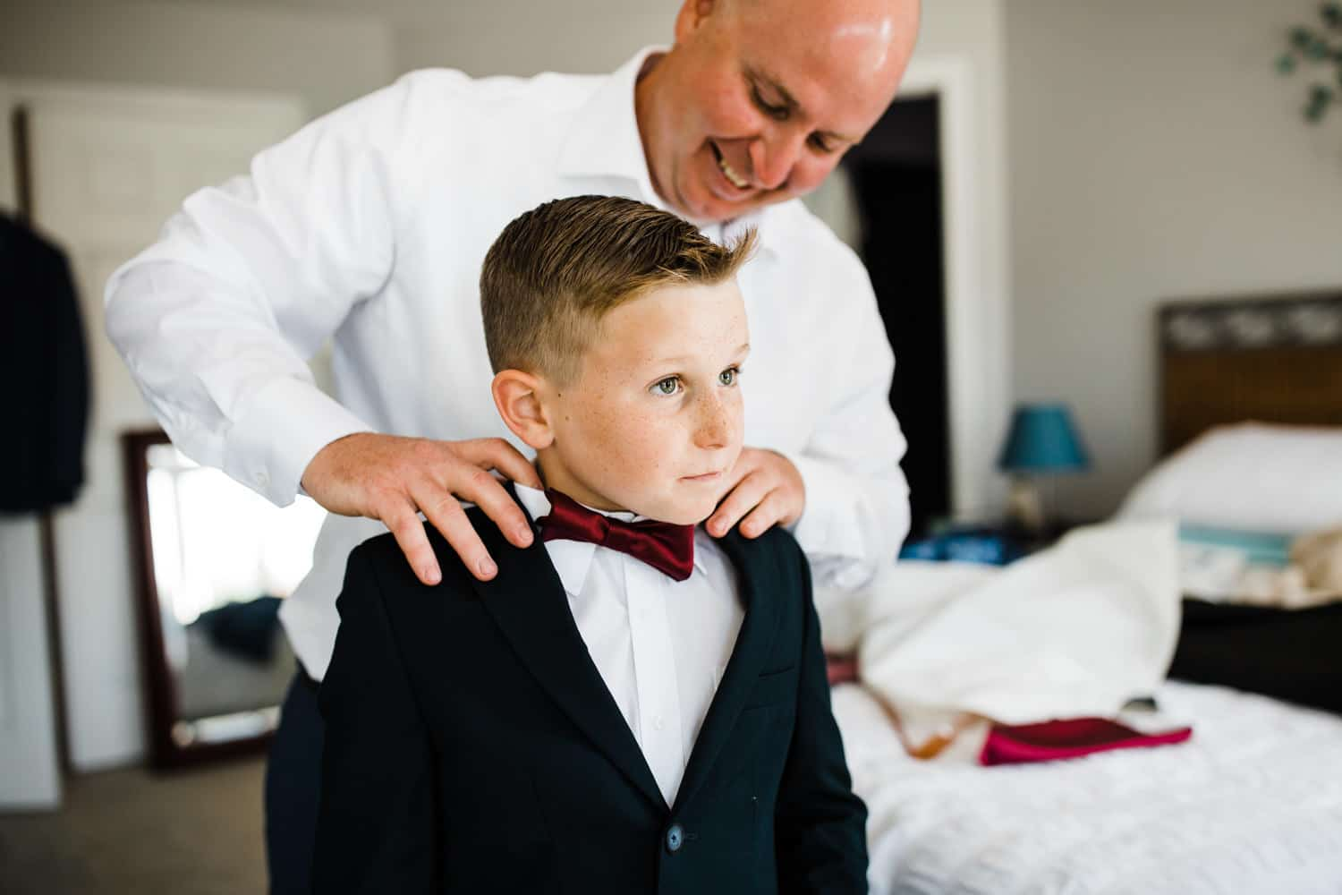 man helps ring bearer with his bow tie