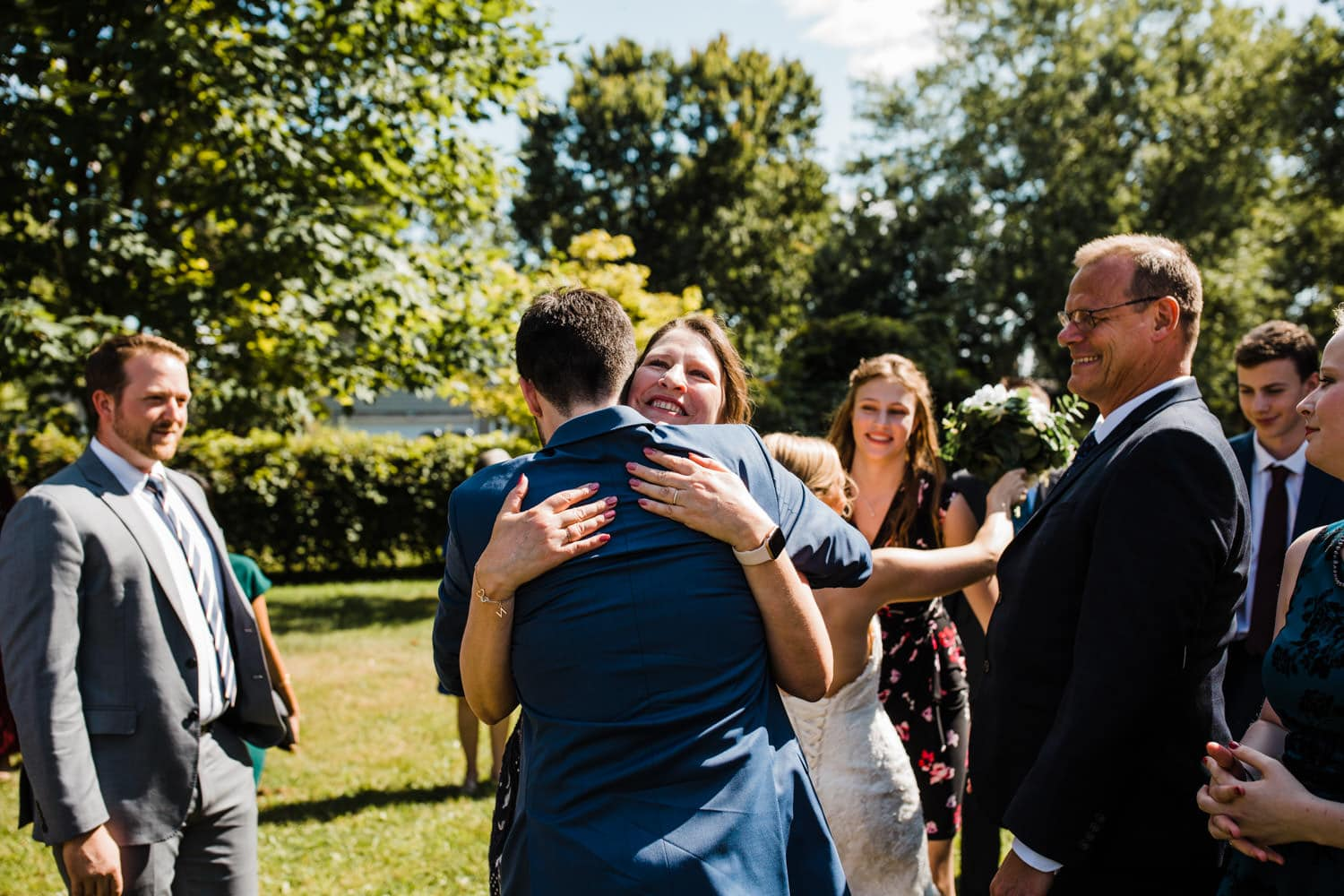 guests hug groom after outdoor wedding ceremony