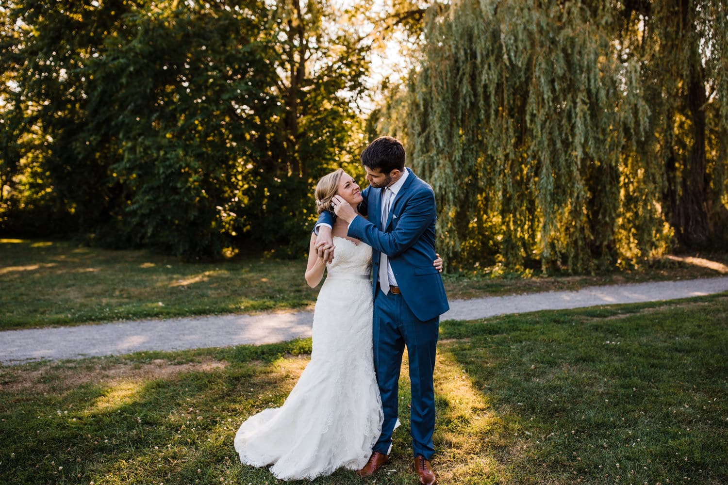 bride and groom embrace by willow tree - glebe community centre wedding