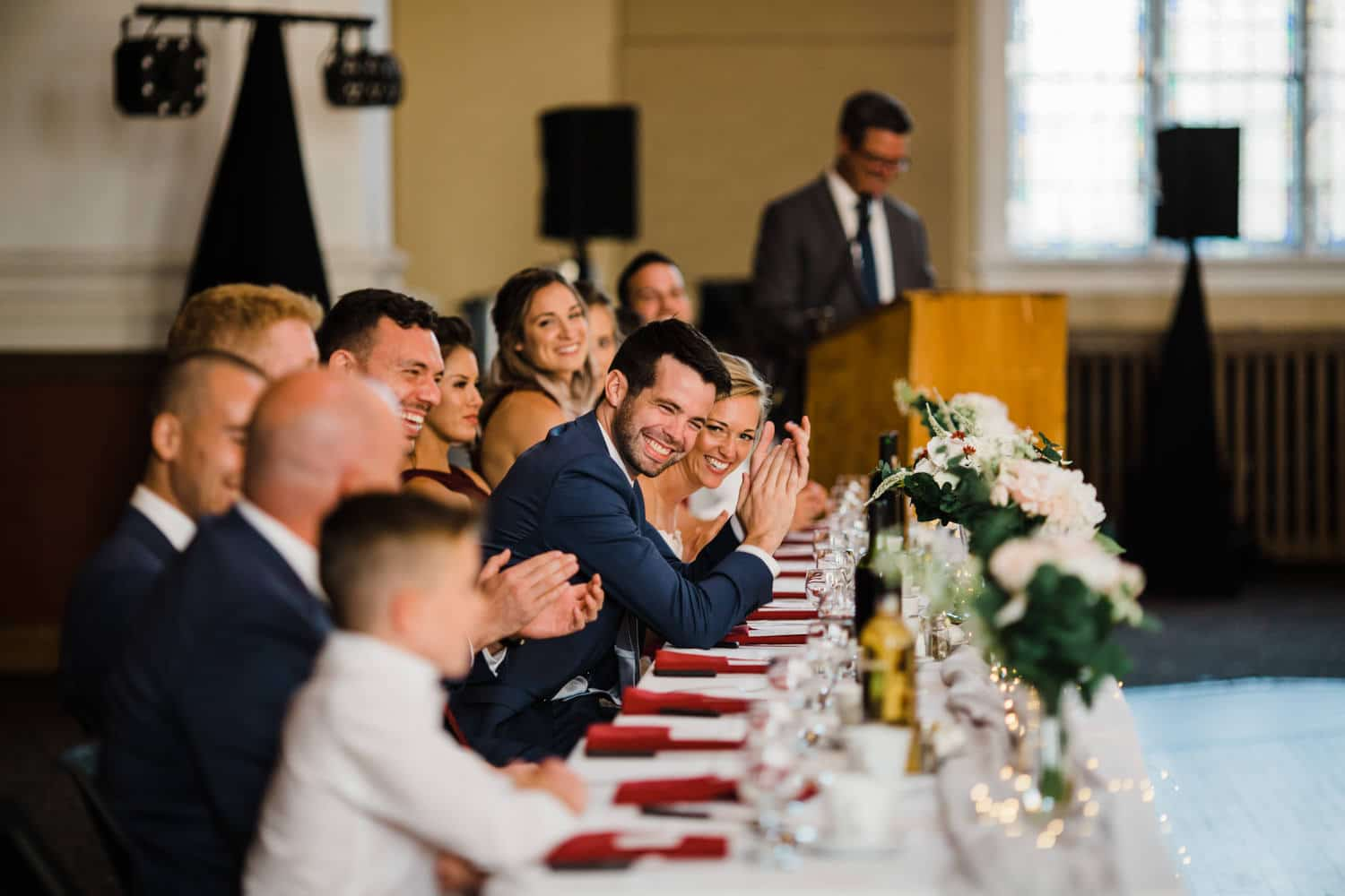 bride and groom laugh during wedding speeches - glebe community centre wedding