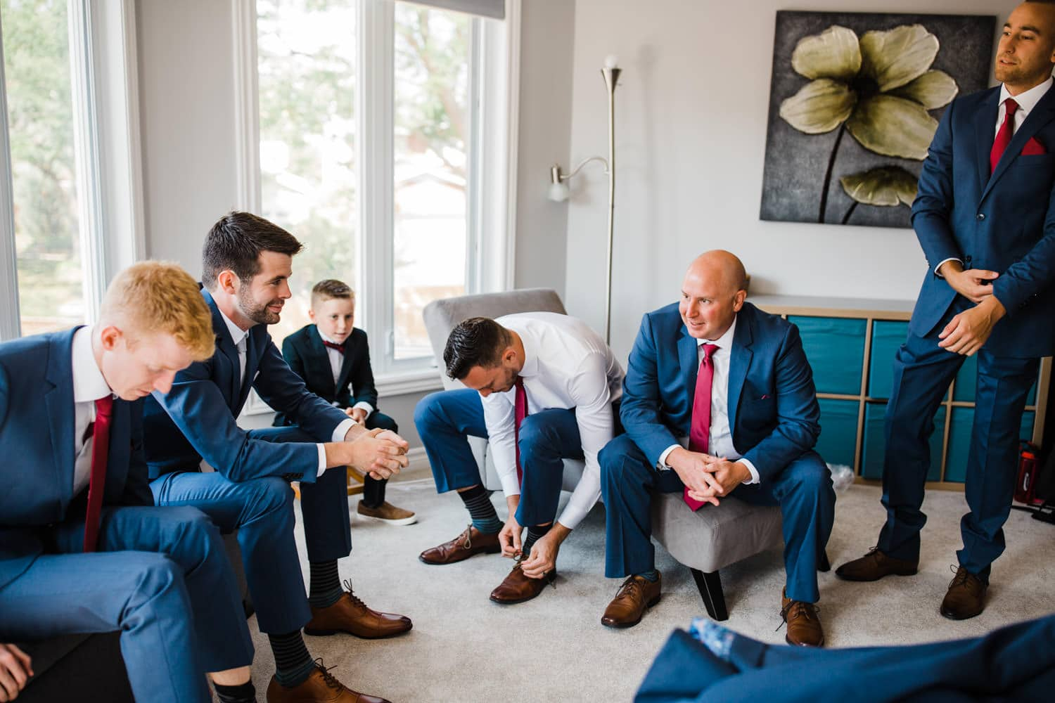 groomsman sit together and tie their shoes - groom prep