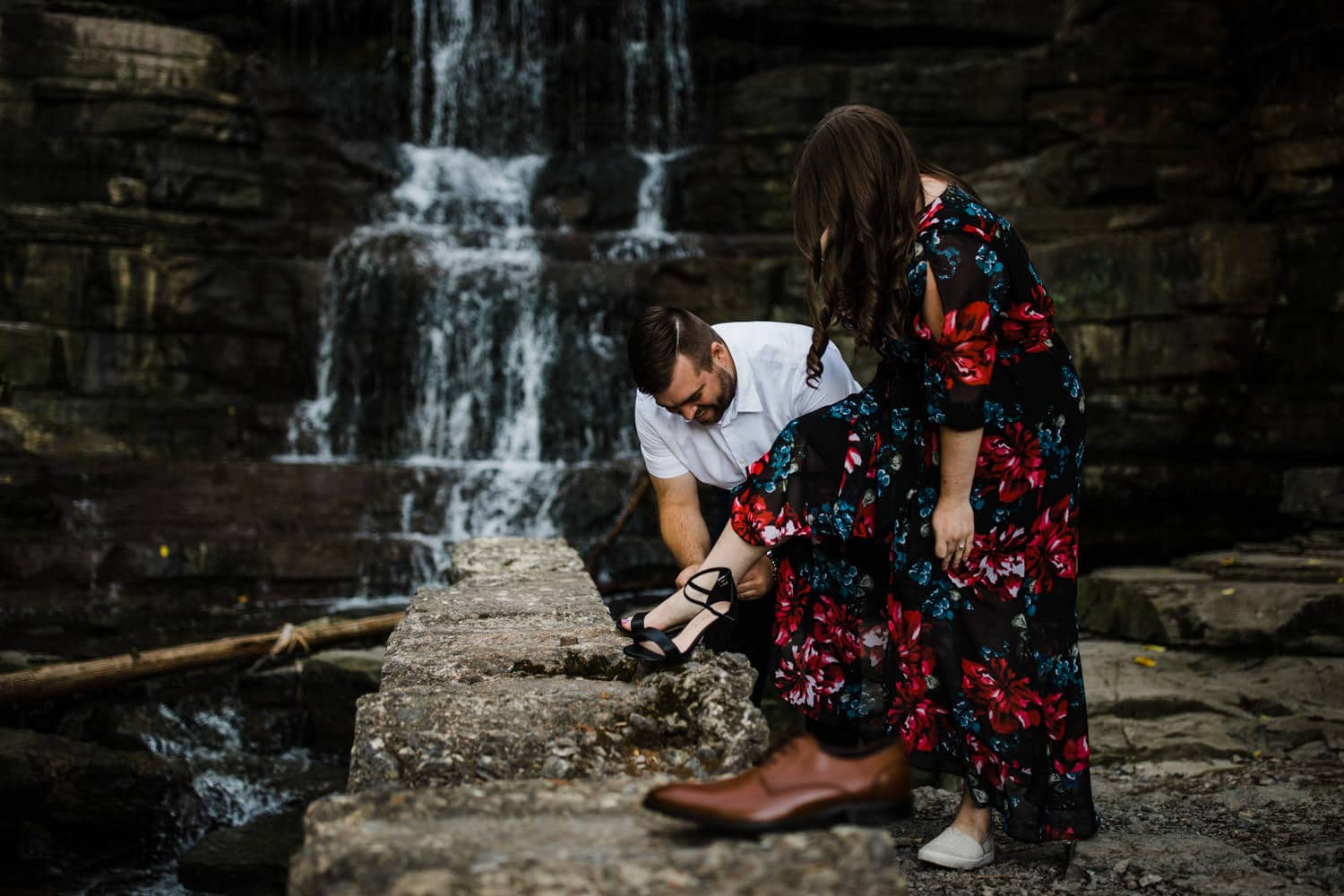 man helps woman put on her shoes by a waterfall - princess louise falls