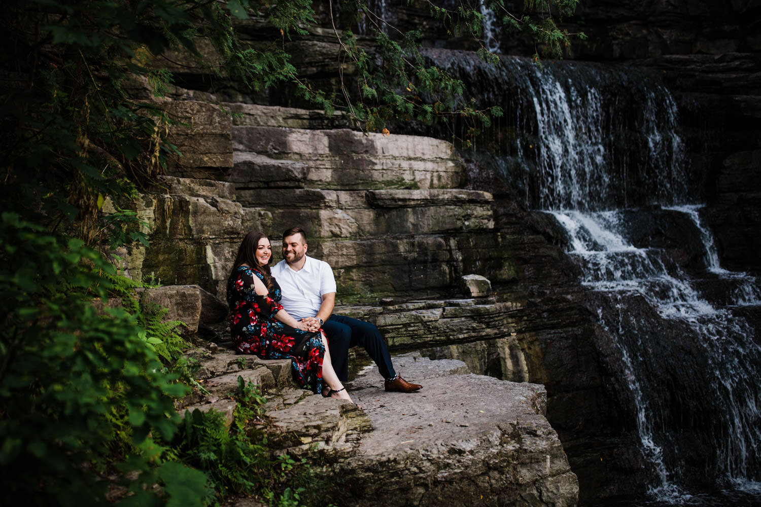 couple sit by waterfall together - princess louise falls engagement photos