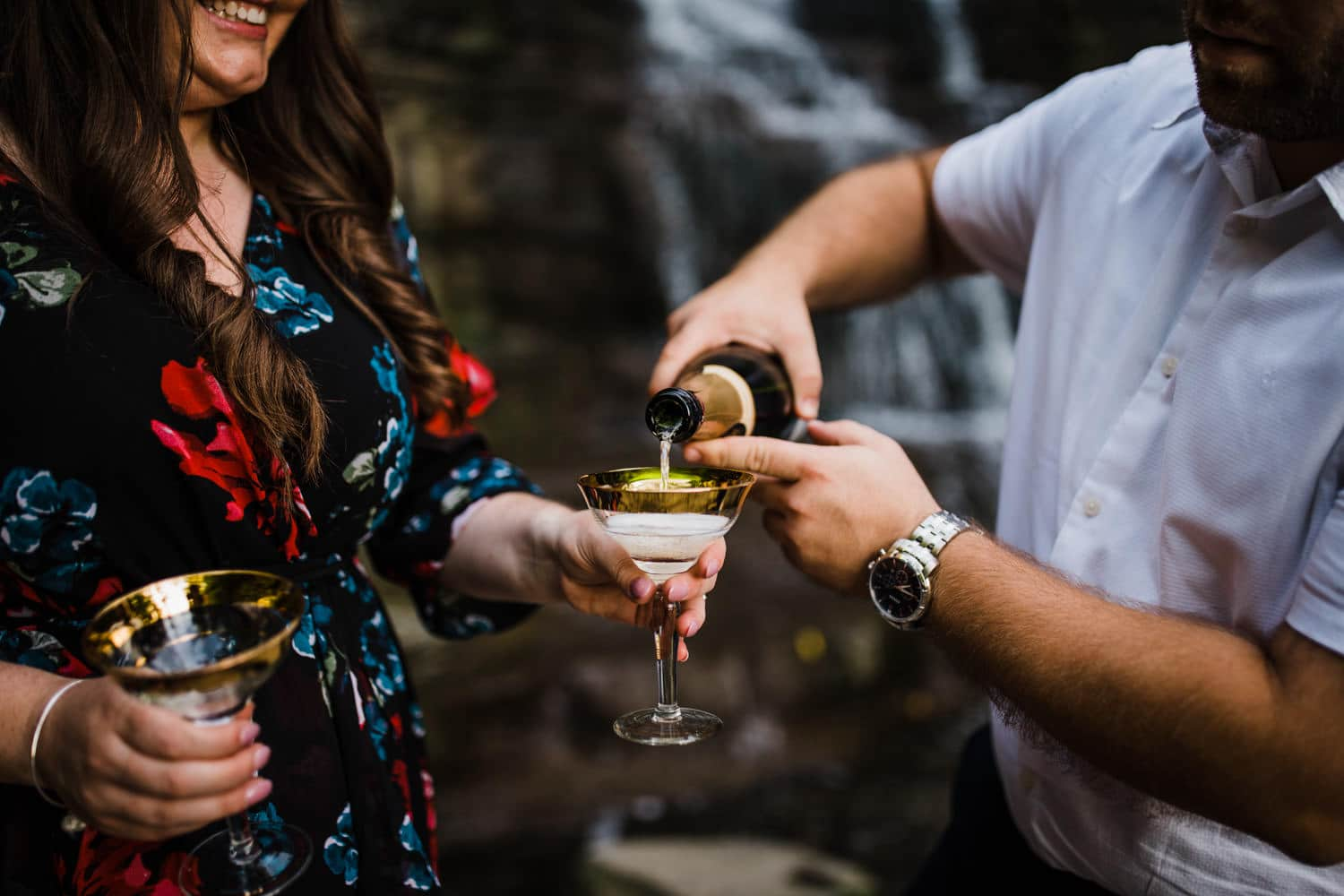 couple pour champagne beside waterfall