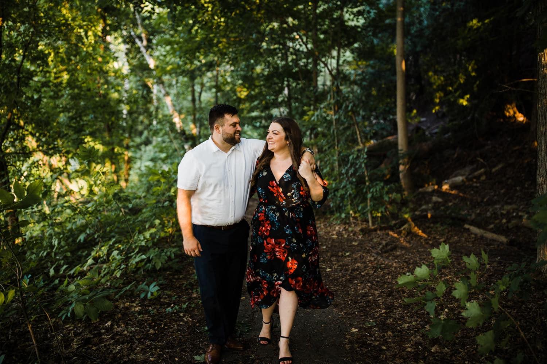 couple walk through wooded area - ottawa engagement photographer