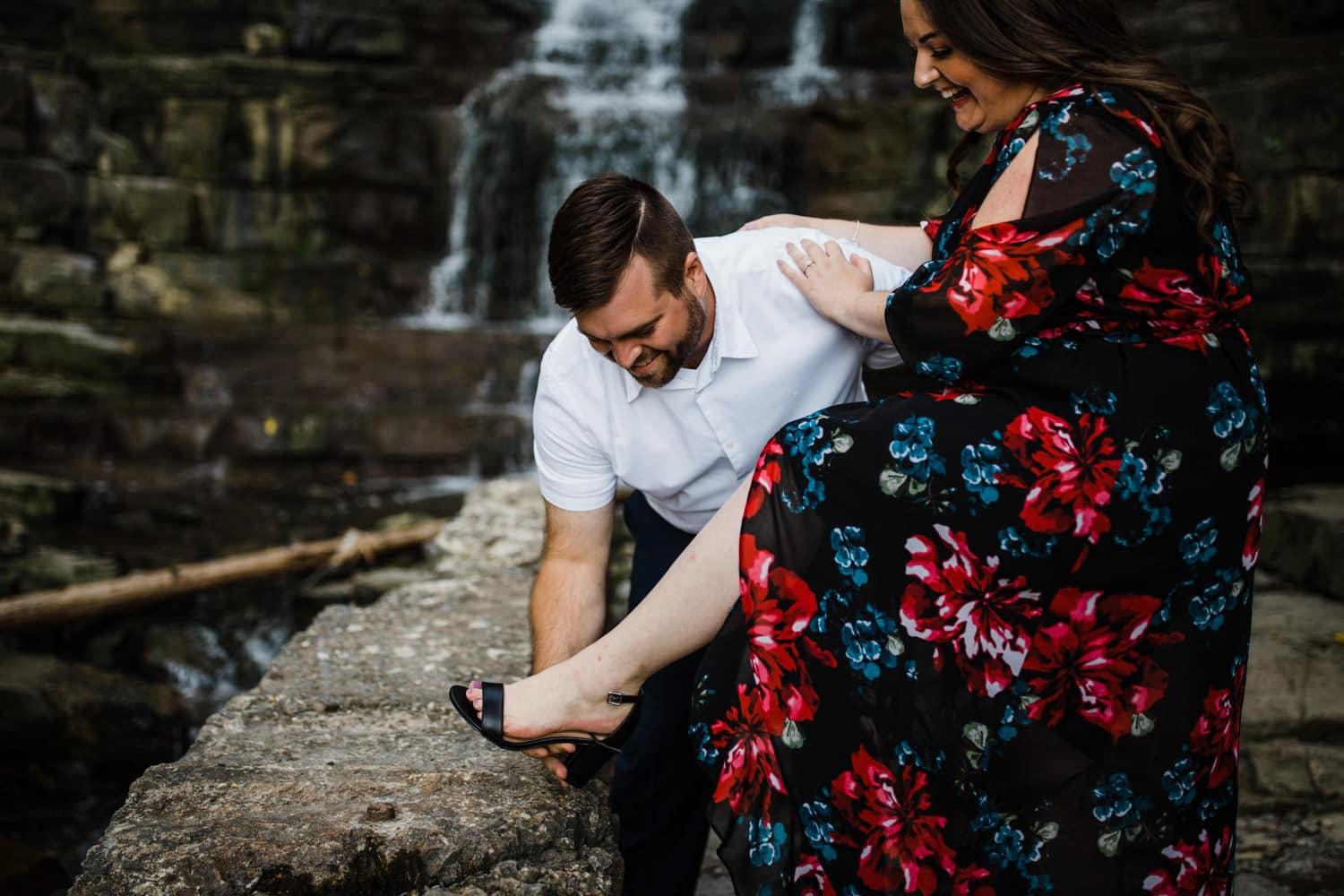 man helps woman put on her shoes by a waterfall