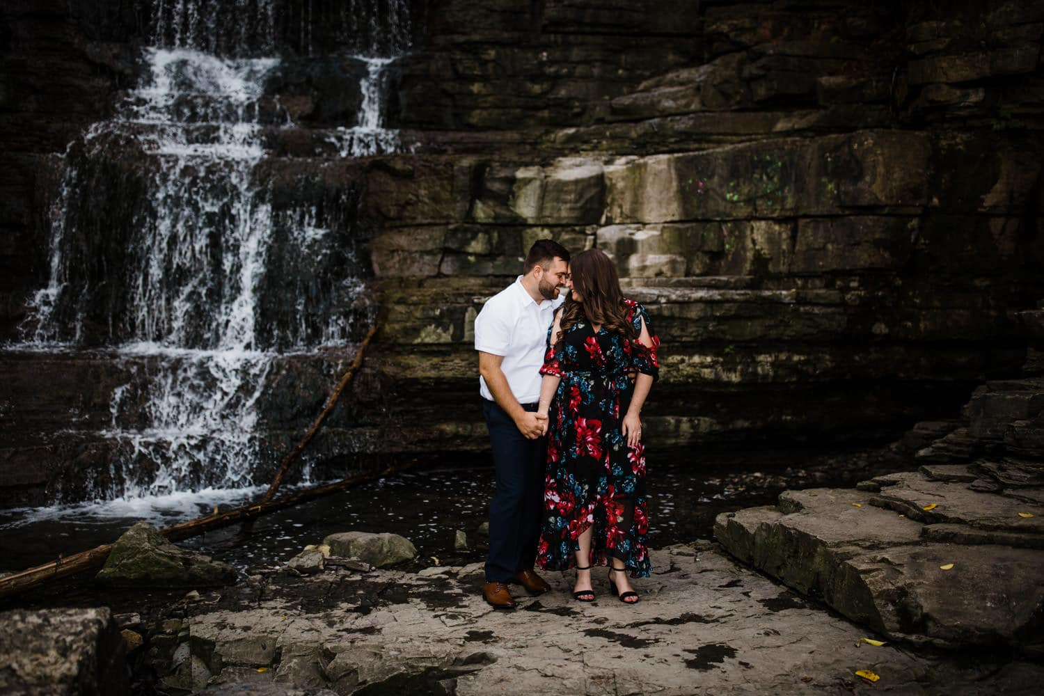 engaged couple stand by waterfall - princess louise falls engagement session
