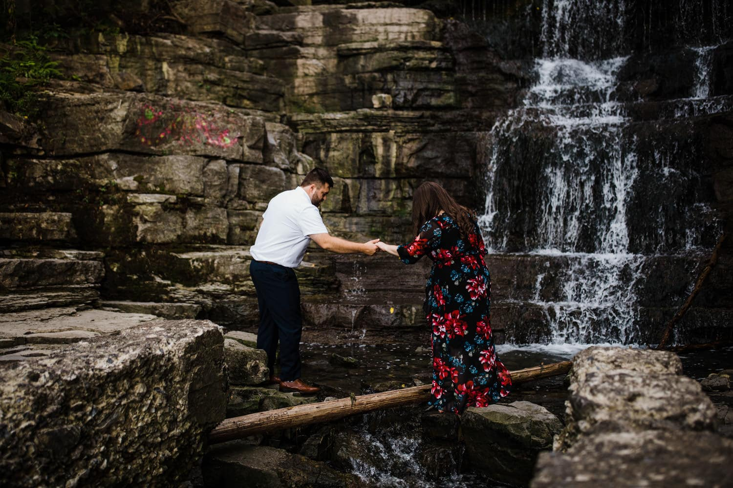 man helps woman cross over waterfall - princess louise falls engagement session
