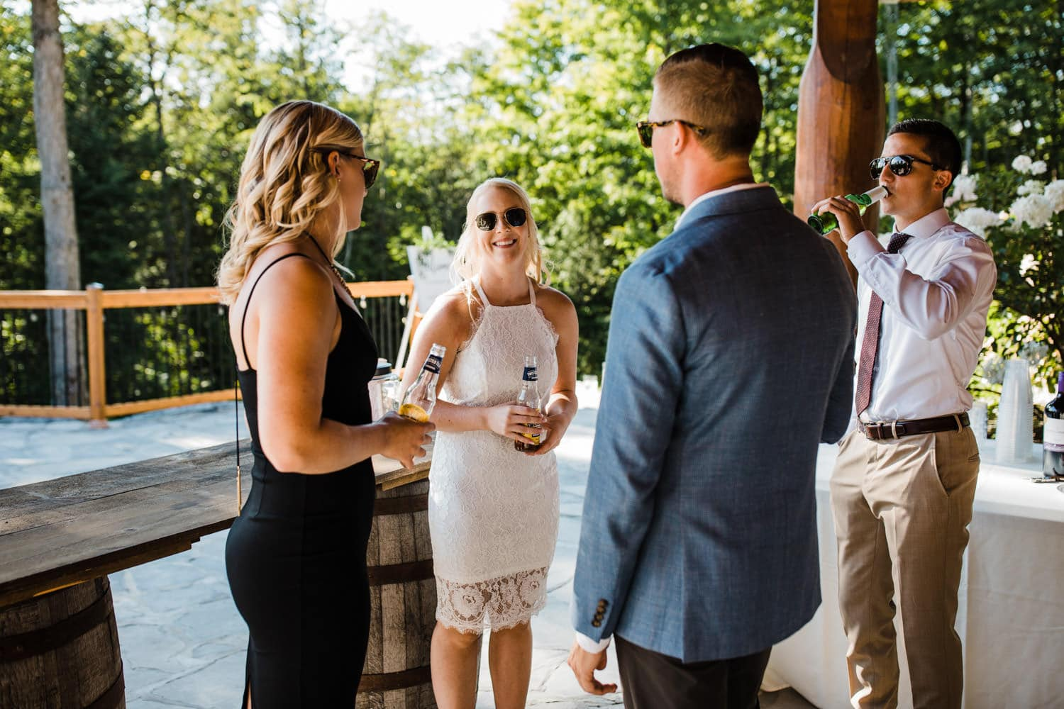 friends hang out on stone patio and drink beers - surprise wedding ottawa
