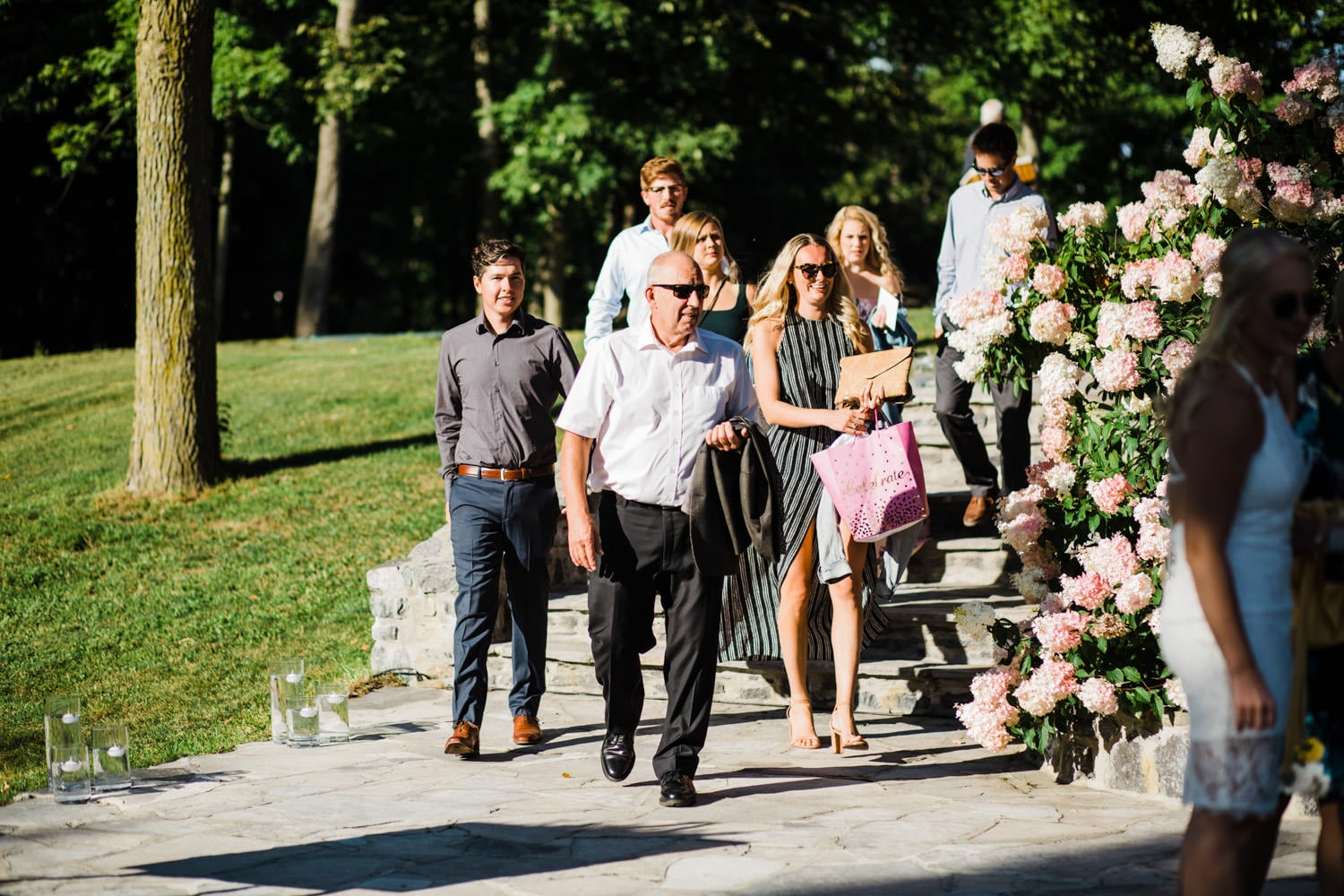 guests arrive for surprise wedding on outdoor stone patio