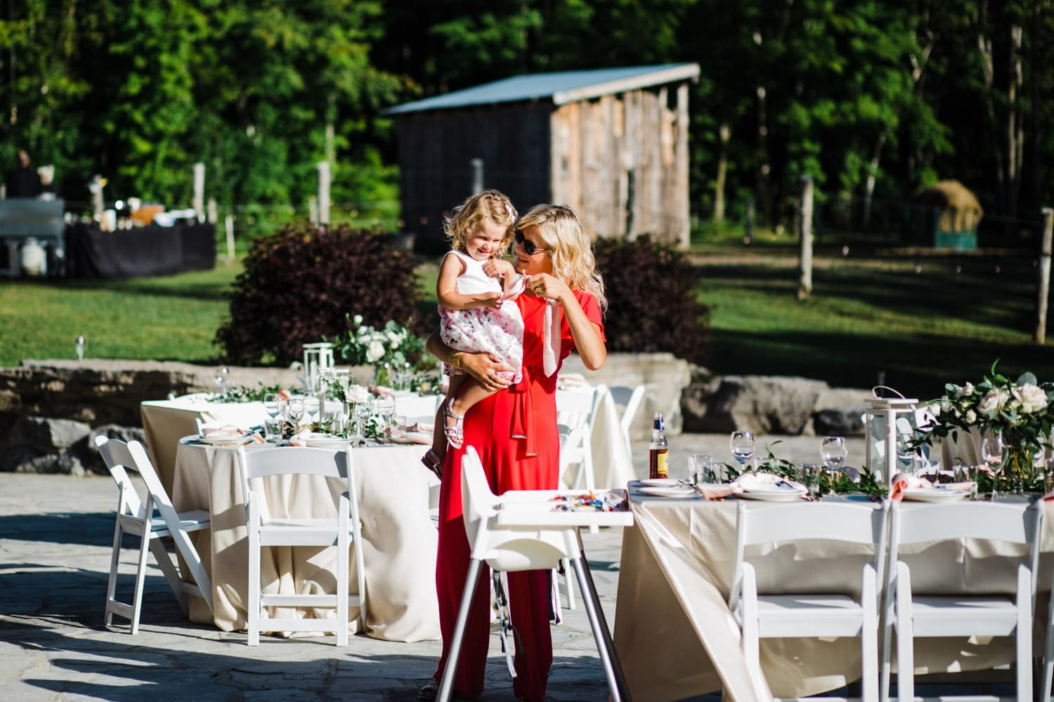 woman and child look at table decor at outdoor wedding