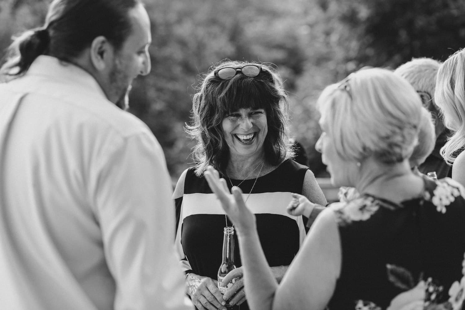 woman laughs as guests mingle at outdoor surprise wedding