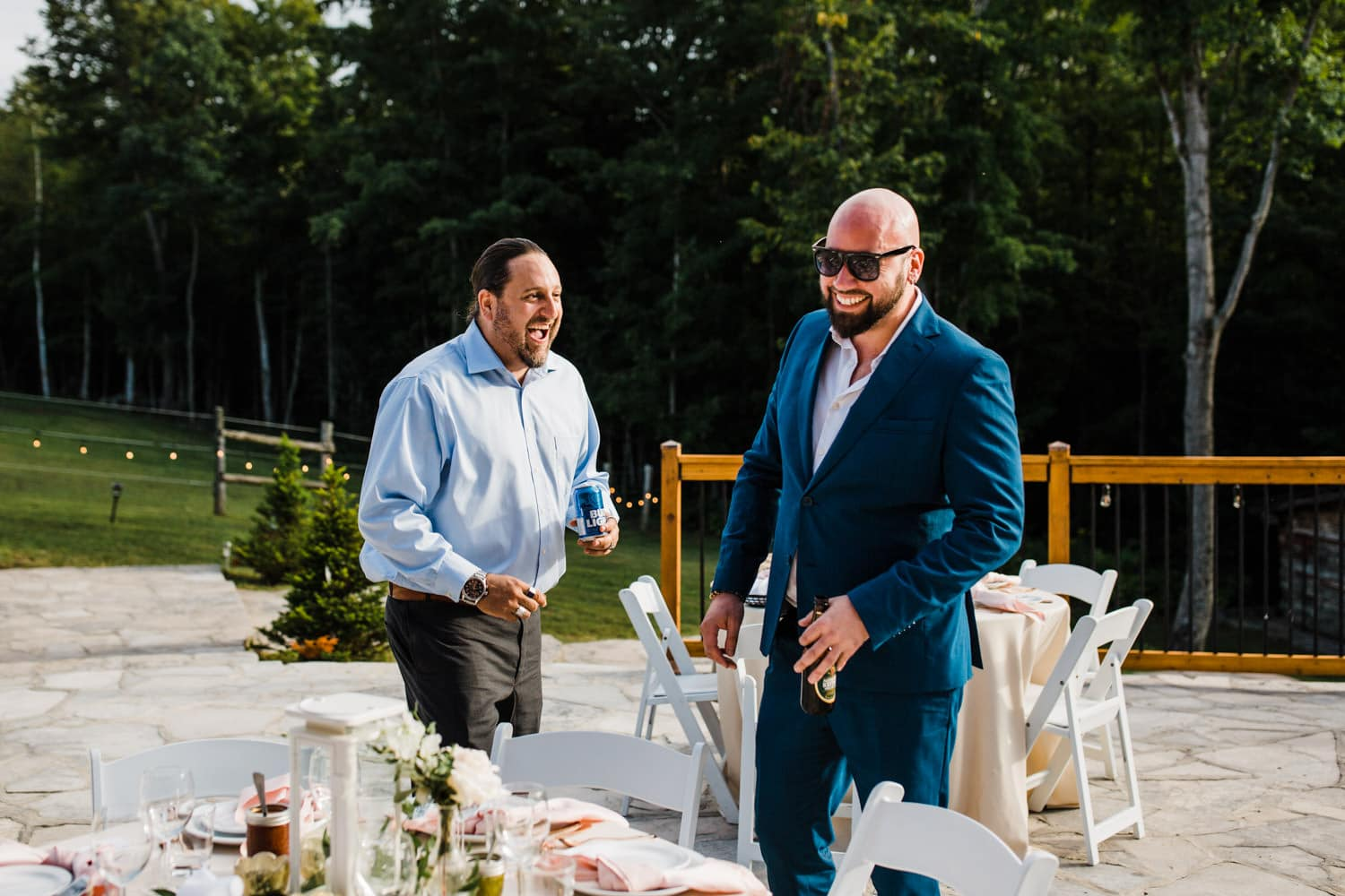 guests laugh together at outdoor surprise wedding on stone patio