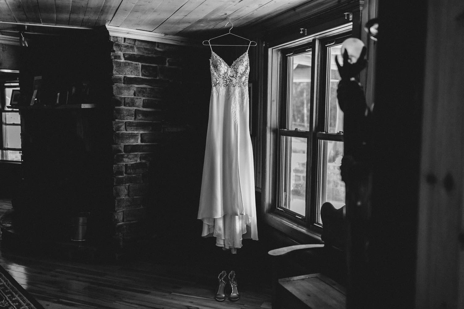 black and white photo of wedding gown hanging in log home