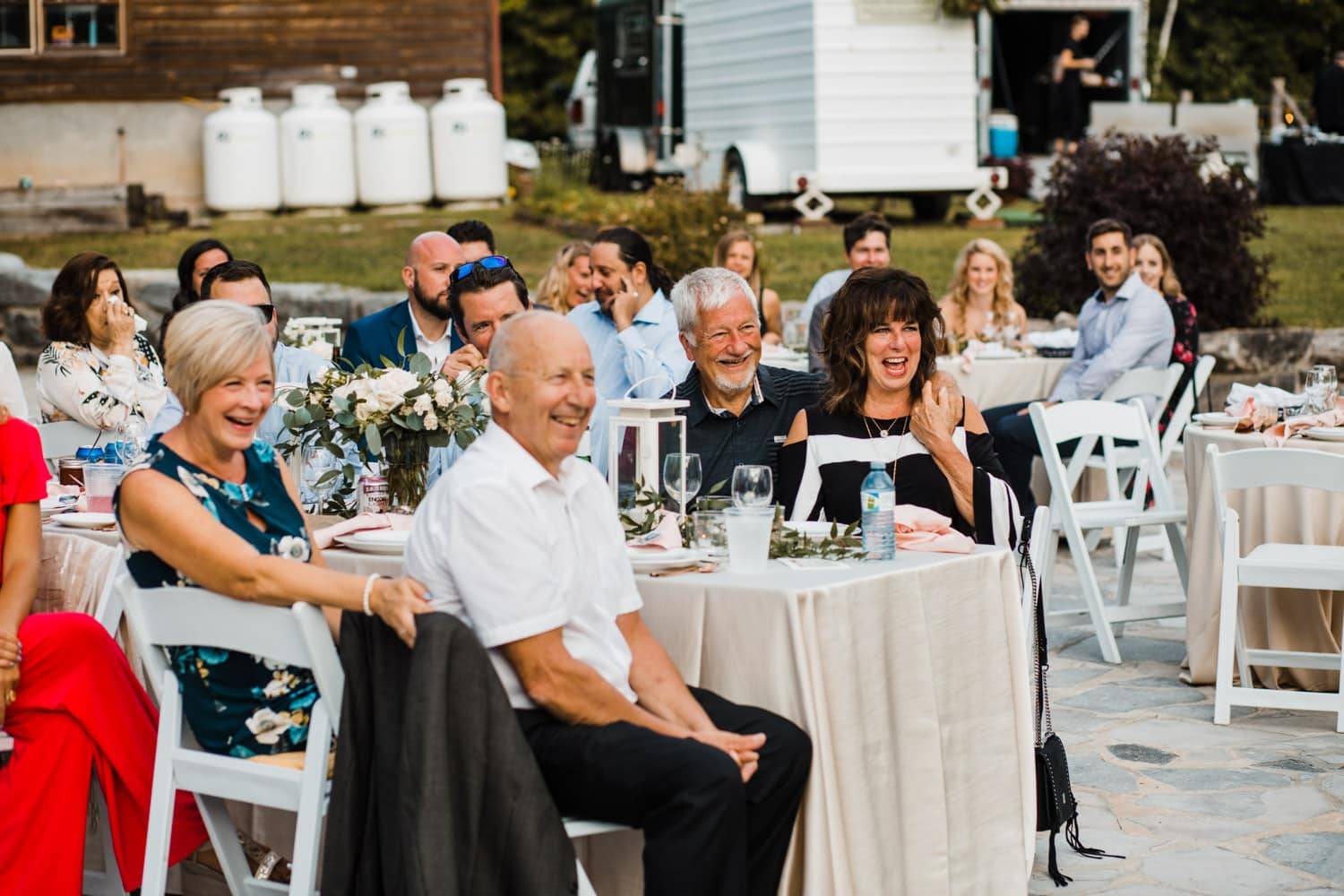guests laugh during outdoor surprise wedding