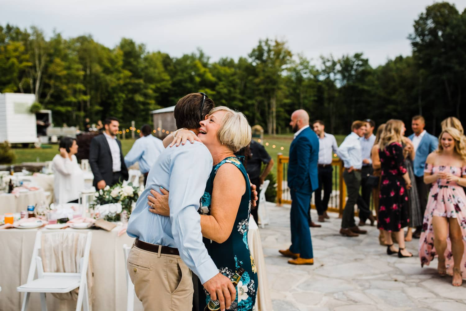 guests hug and react after outdoor wedding ceremony