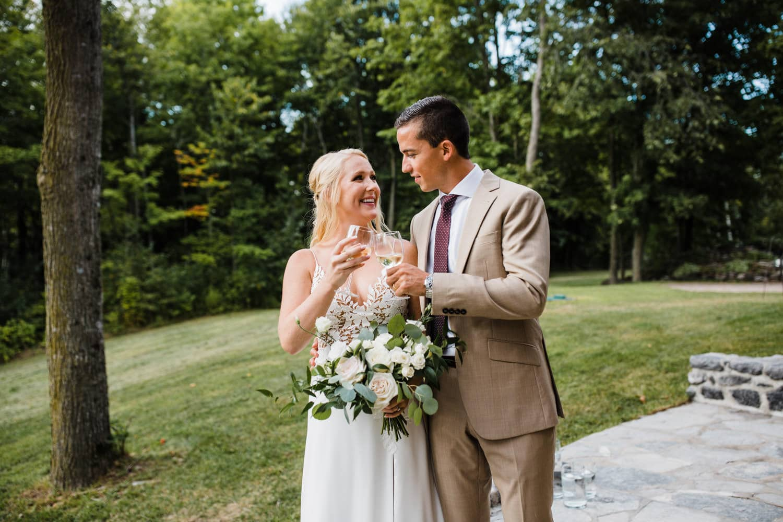 bride and groom cheers after outdoor wedding ceremony
