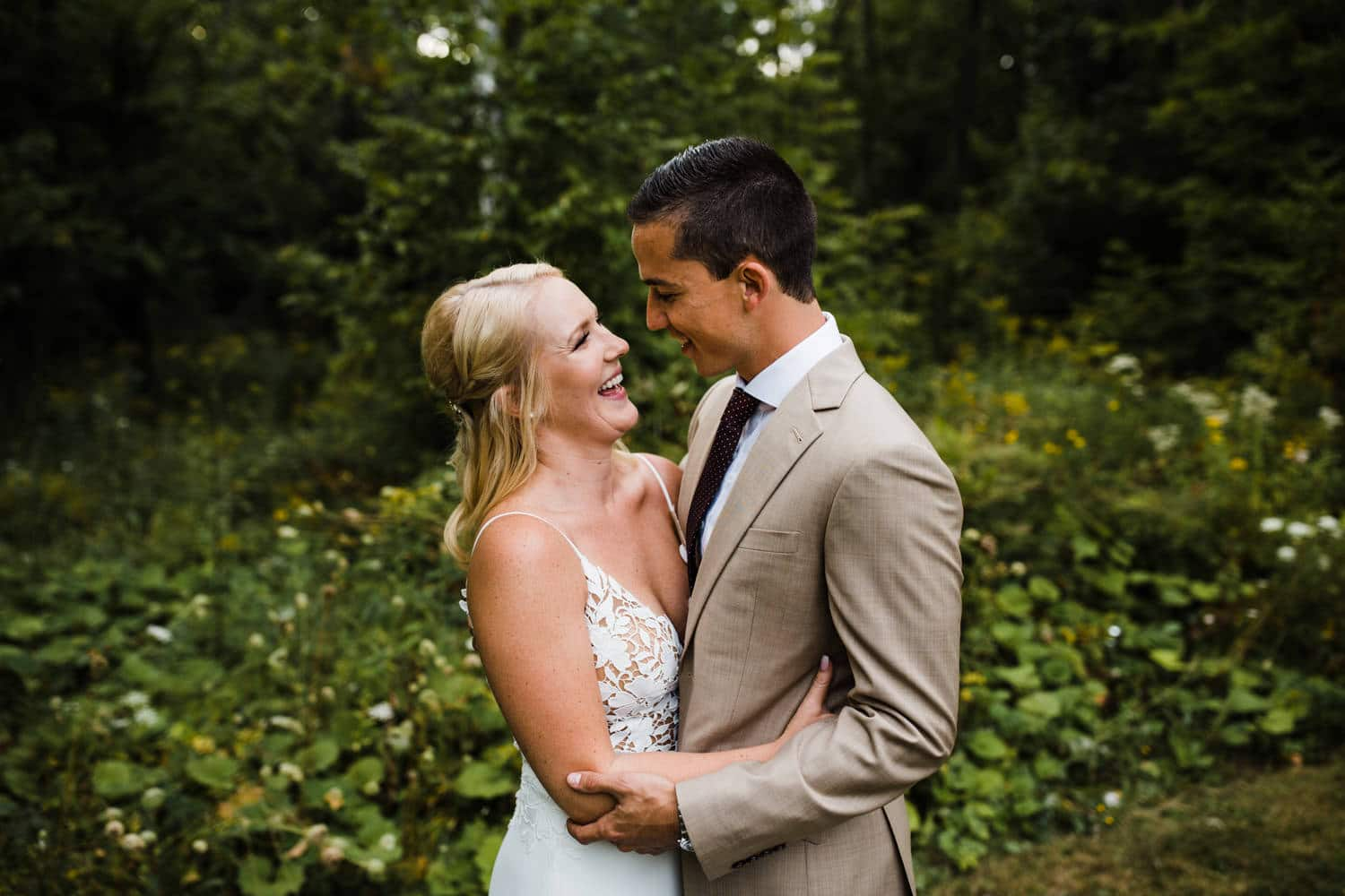 bride and groom laugh together after outdoor surprise wedding ceremony