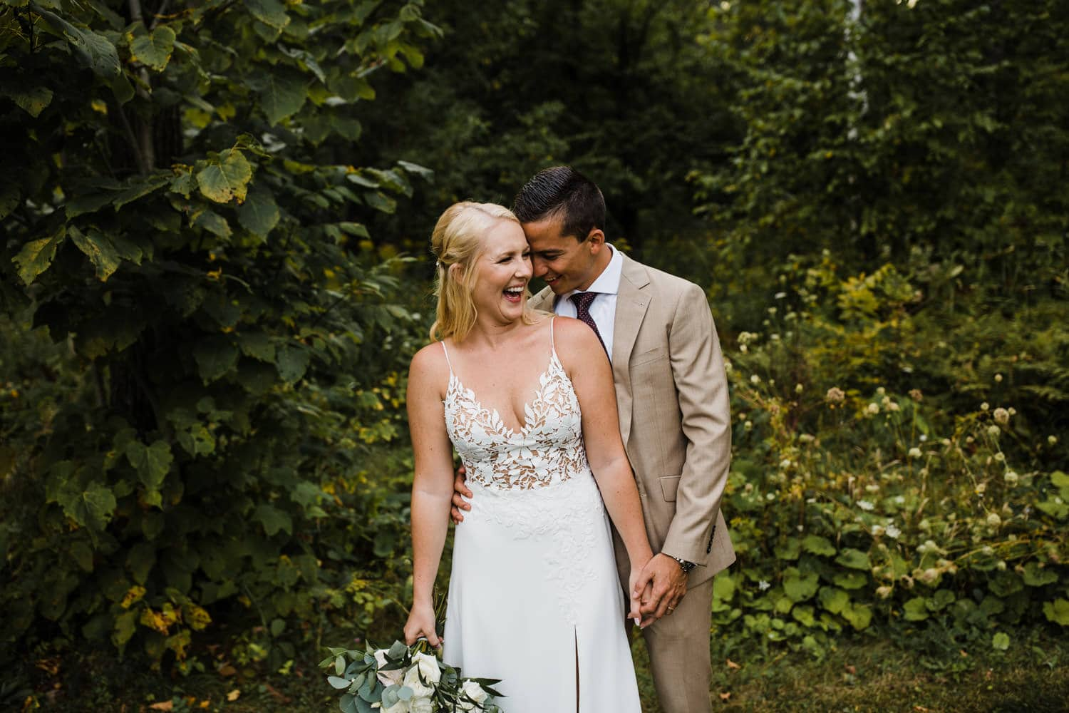 bride and groom laugh together outside - ottawa wedding photographer