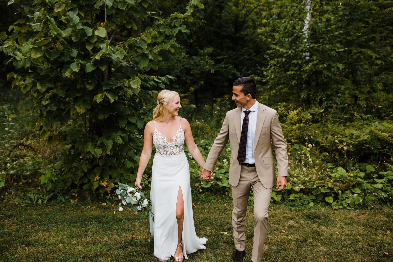bride and groom walk together outside - ottawa wedding photographer