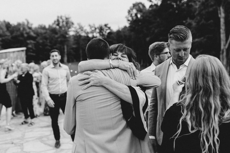 mom hugs groom after outdoor surprise wedding ceremony