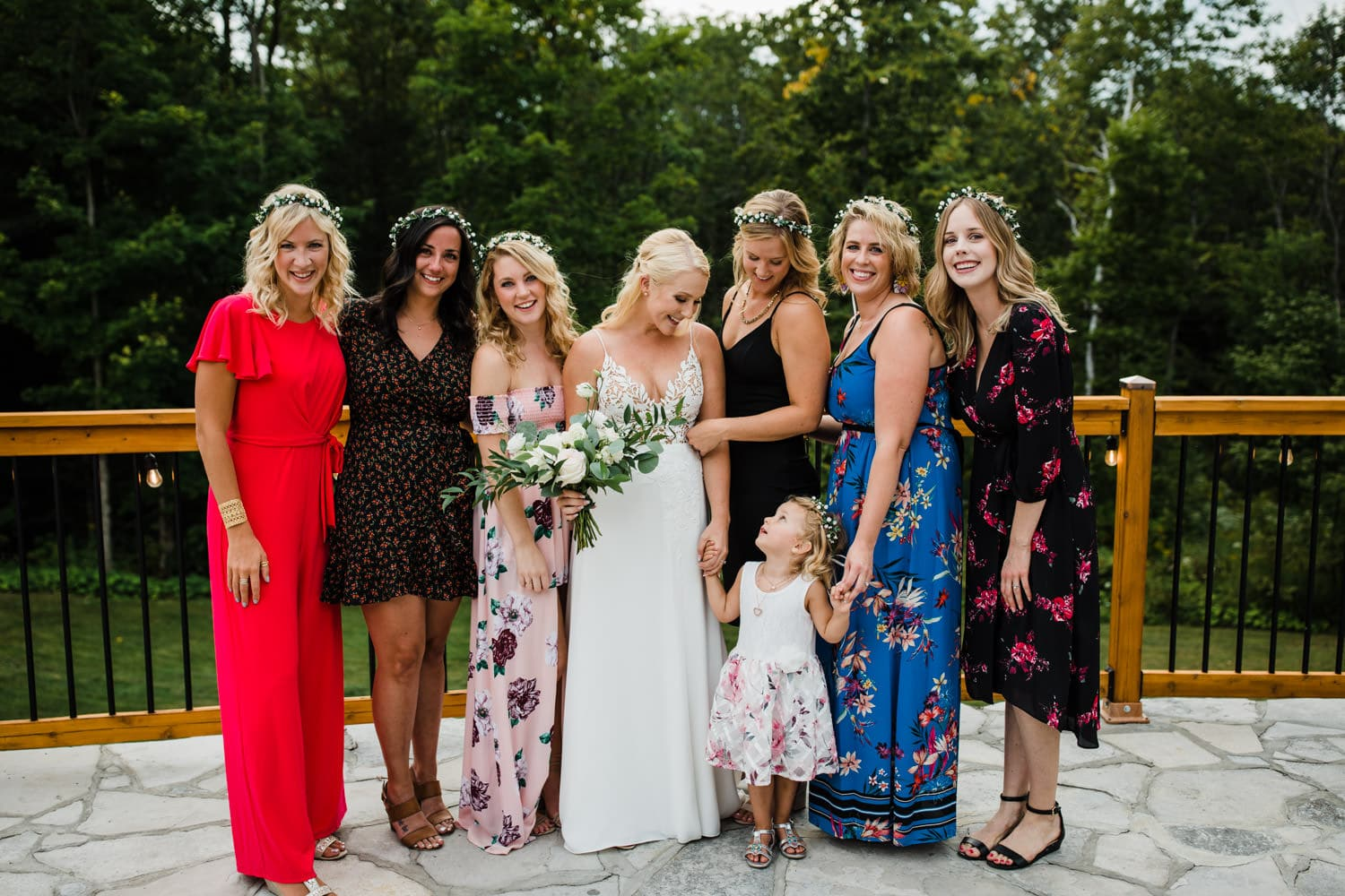 bride stands with her honorary bridesmaids after outdoor wedding