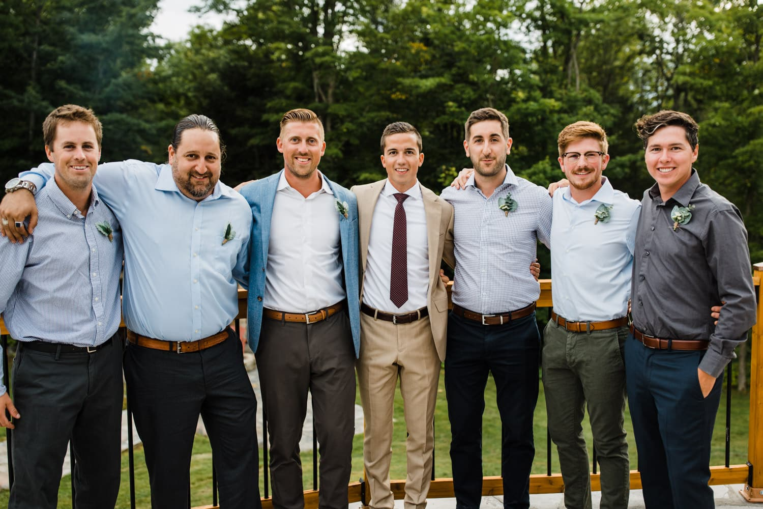 groom stands with his honorary groomsmen after outdoor wedding