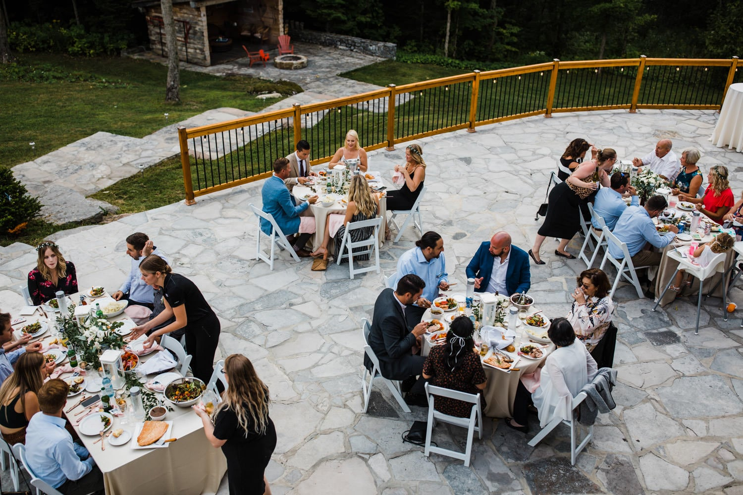 guests sit down for family style dinner at outdoor wedding - ottawa wedding photographer