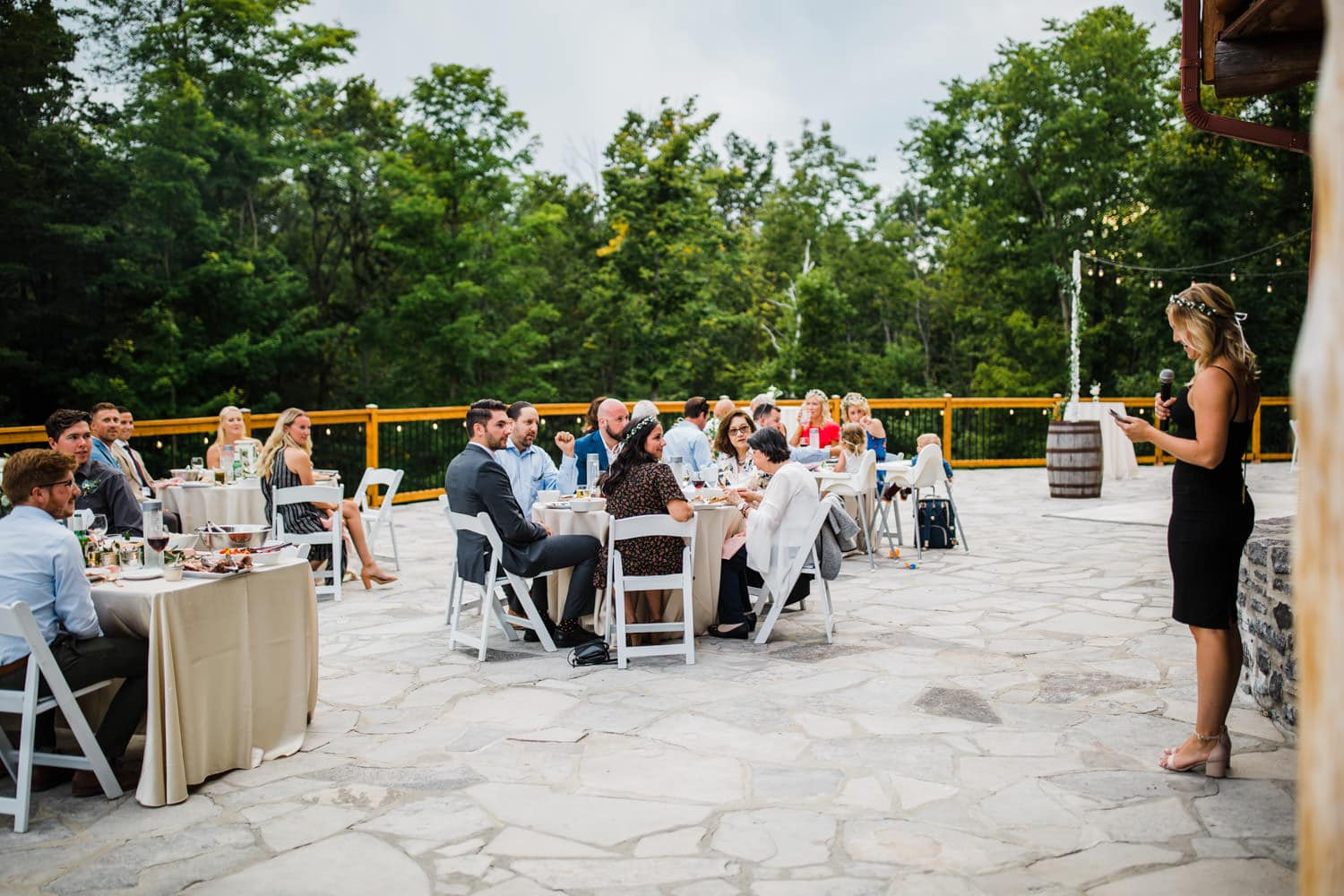 maid of honour stands up for speech on stone patio at outdoor wedding reception - ottawa wedding photographer