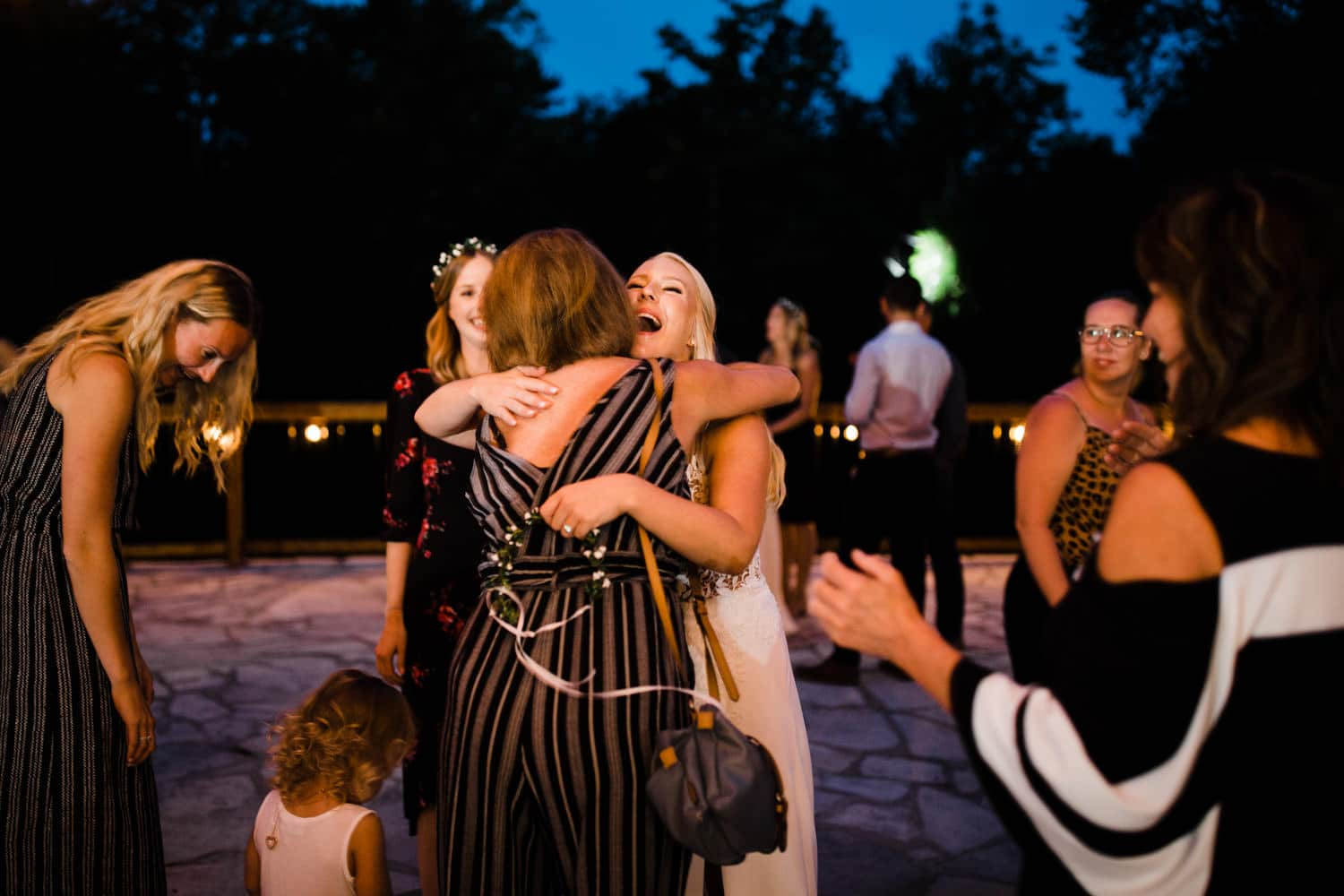 guests hug the bride as they arrive for outdoor wedding reception
