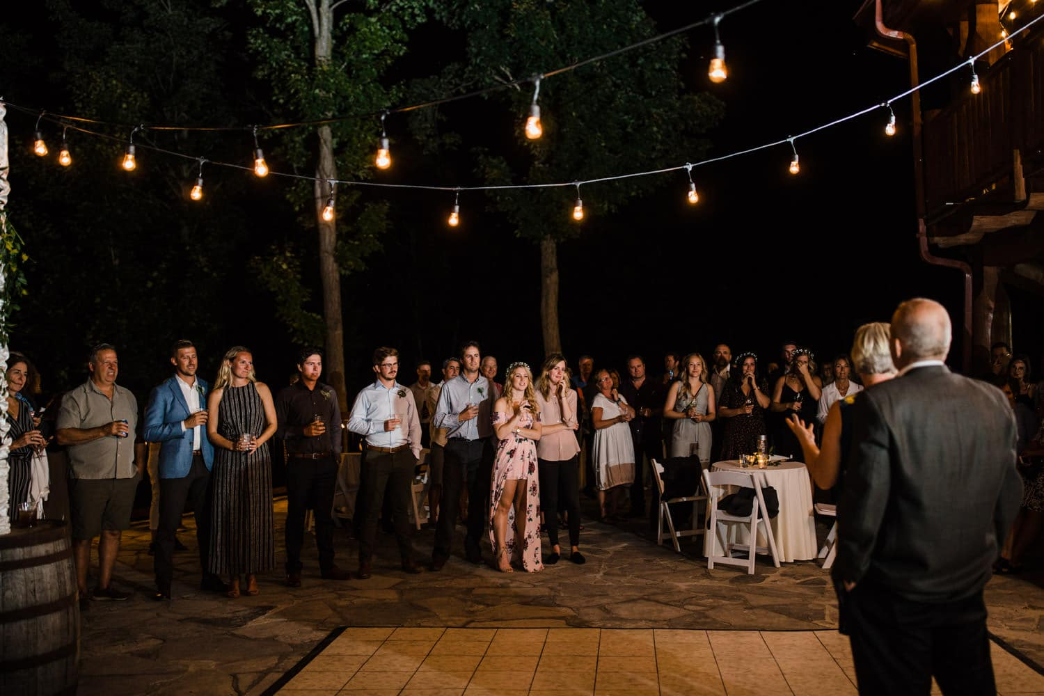 guests listen to speeches at outdoor wedding reception on stone patio