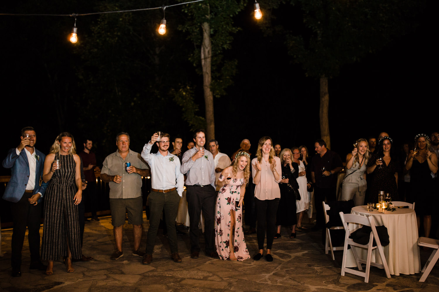guests laugh during speeches at outdoor wedding reception