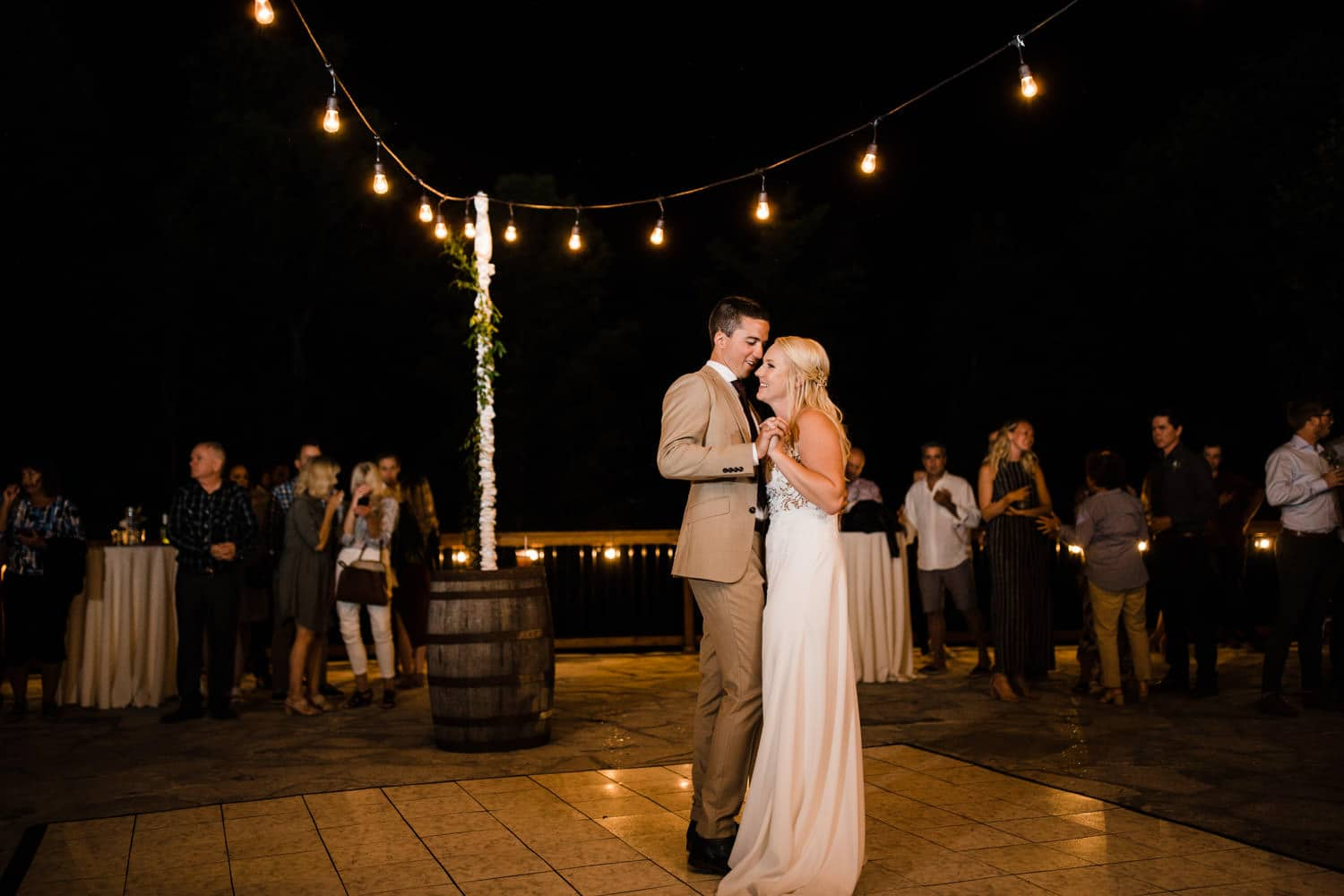 bride and groom first dance twinkle lights at outdoor wedding
