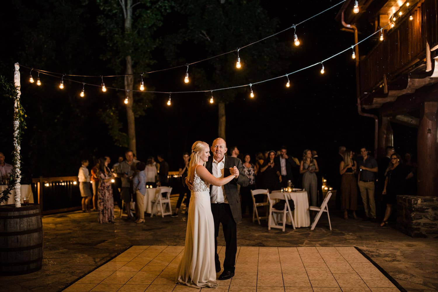 bride dances with her father under twinkle lights at outdoor wedding