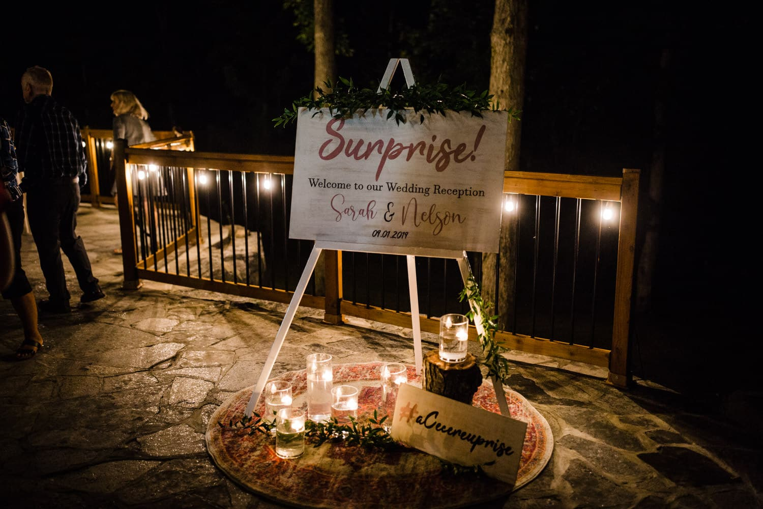 welcome to our surprise wedding sign lit by candles