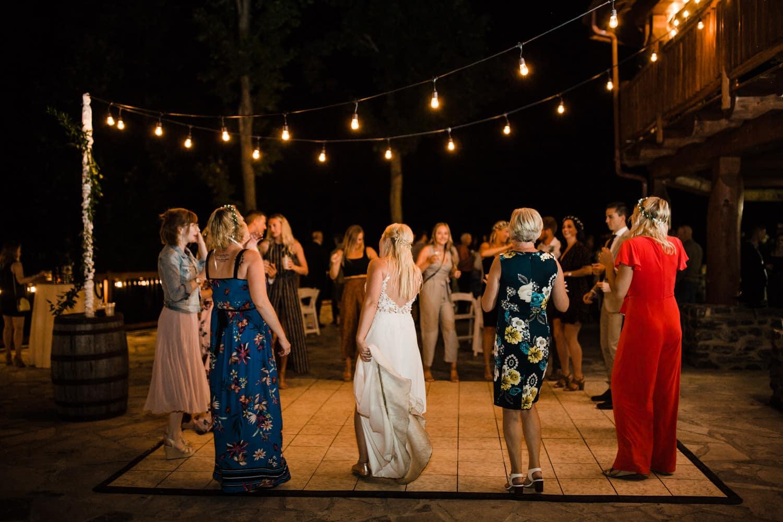 guests dance on outdoor dance floor - twinkle lights over patio