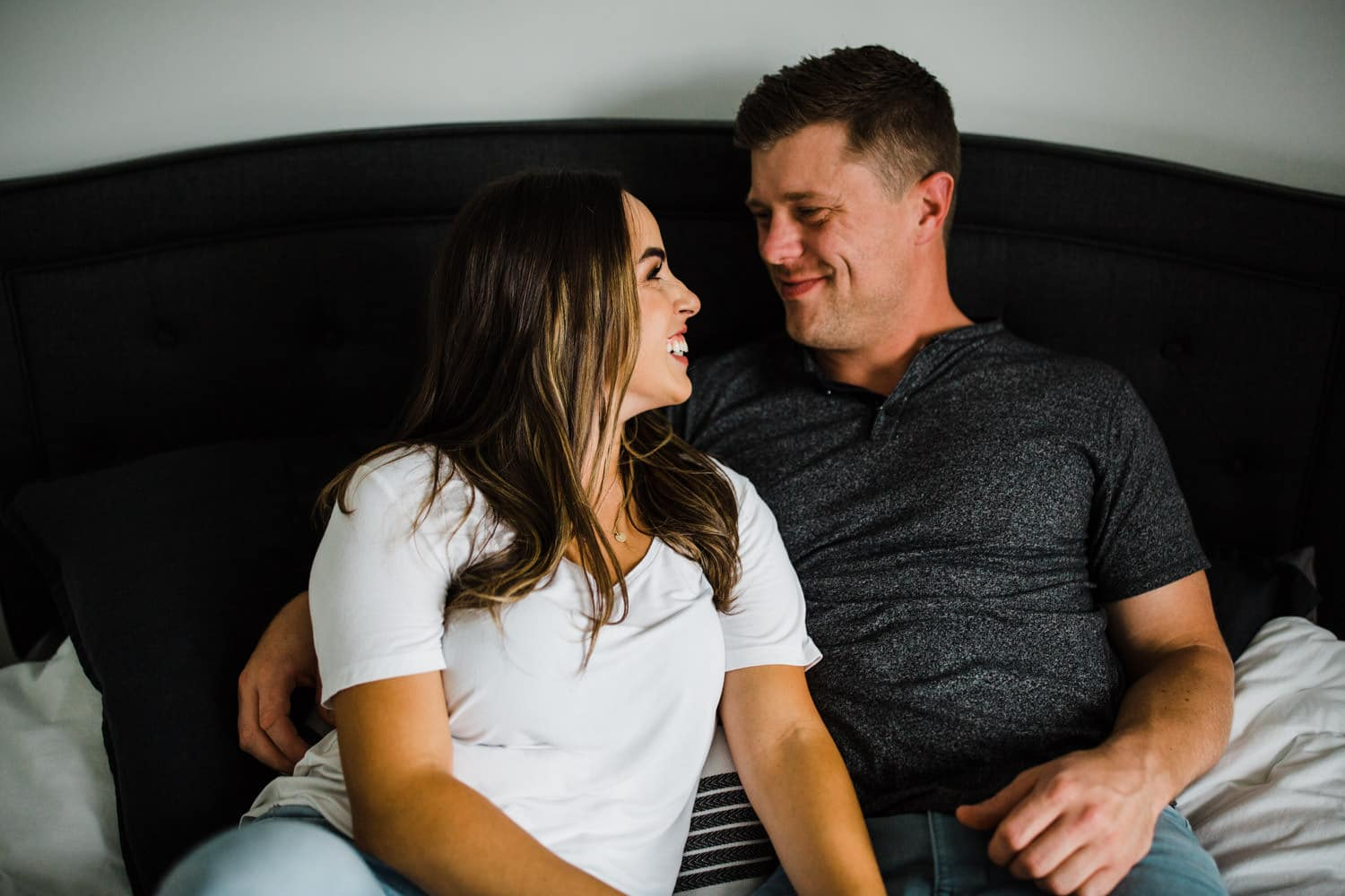 couple laugh together in master bedroom
