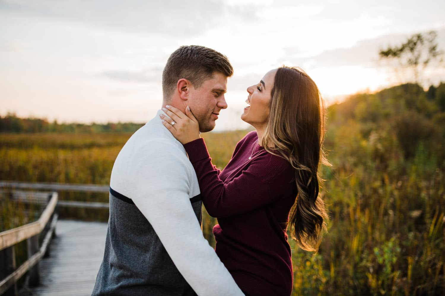 couple laugh together during golden hour - mer bleue engagement
