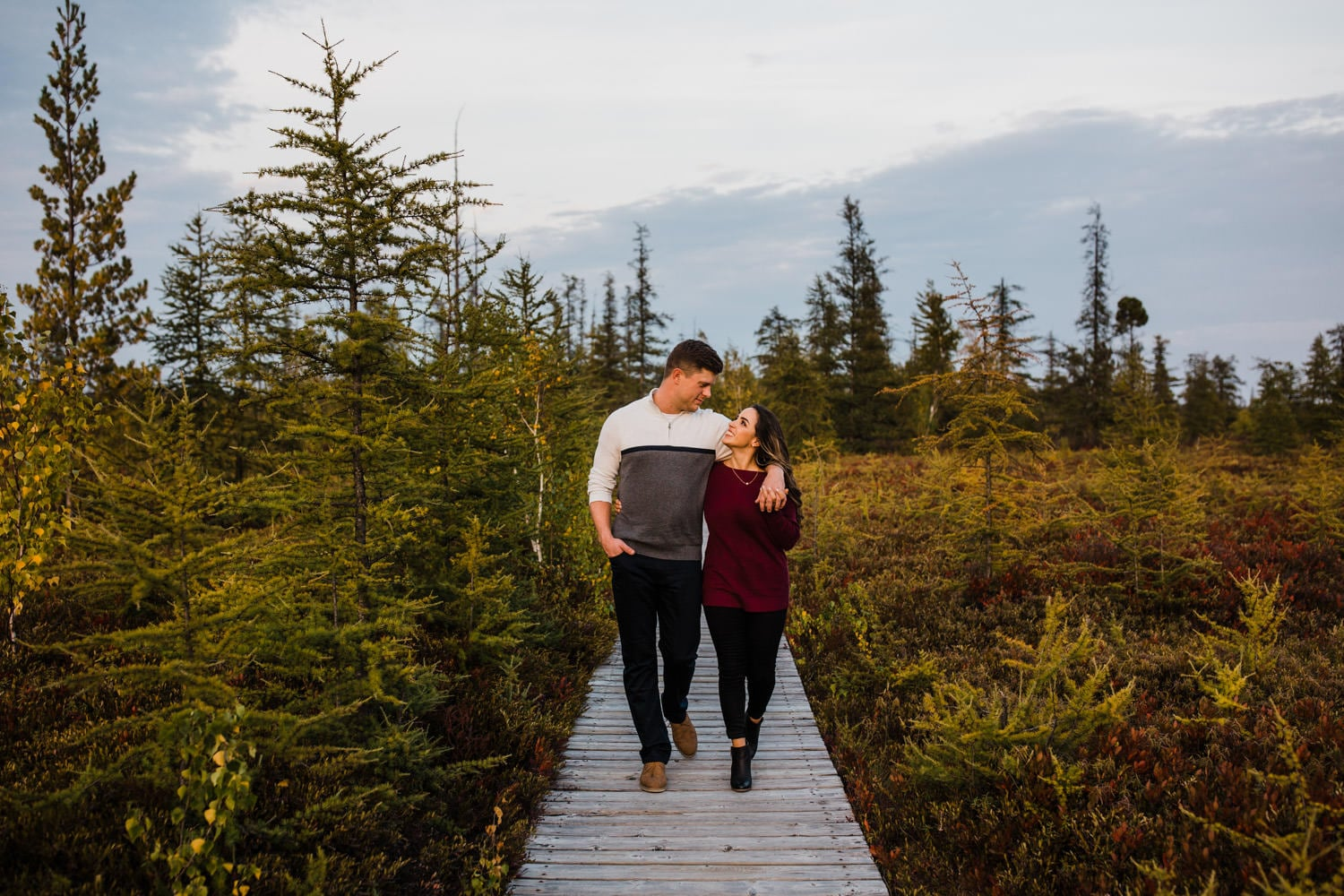 couple walk on boardwalk together during ottawa fall engagement
