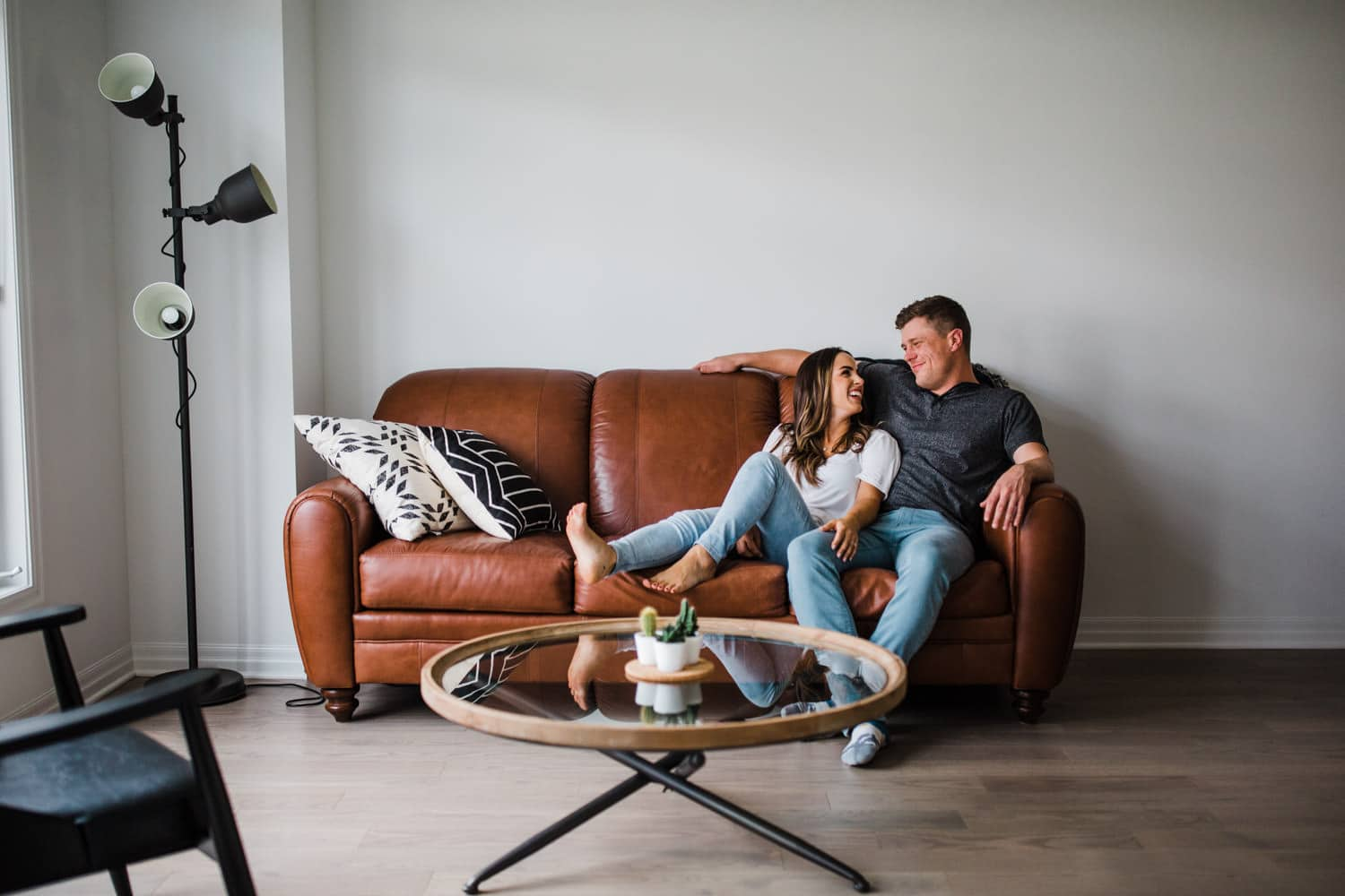 couple hang out on leather couch together - ottawa in home engagement