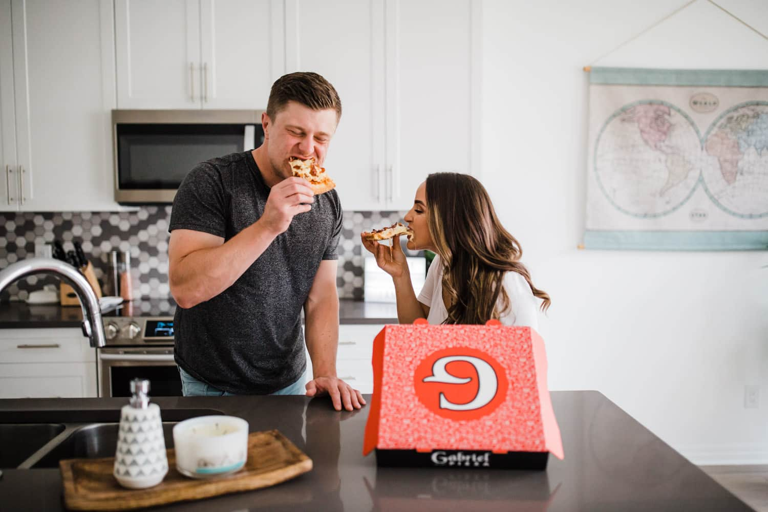 couple eat pizza together at kitchen island